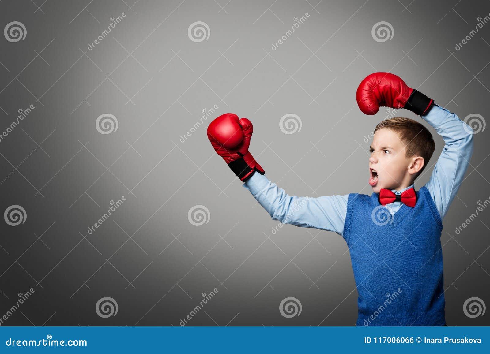 L enfant dans des gants de boxe, boxeur élégant de garçon d enfant élevé arme