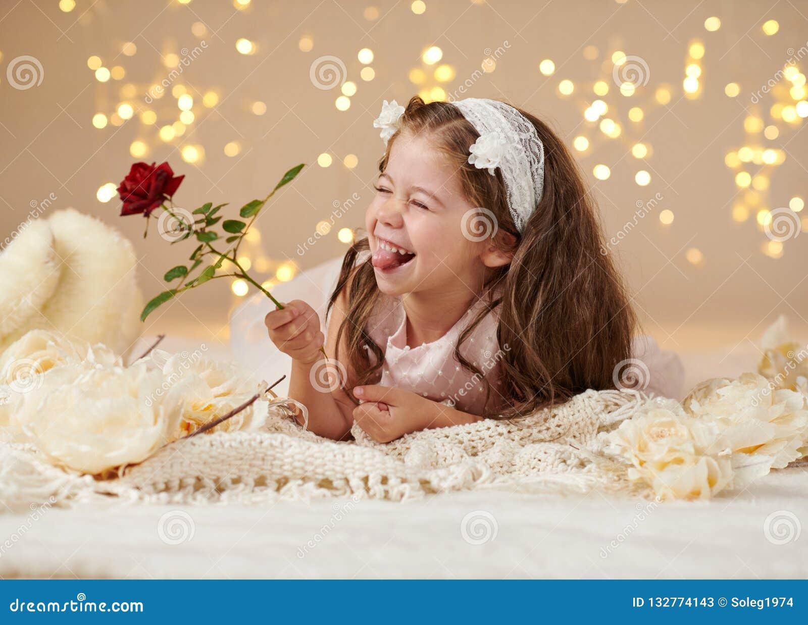 L enfant de fille avec la fleur rose pose dans des lumières de Noël, fond jaune, robe rose