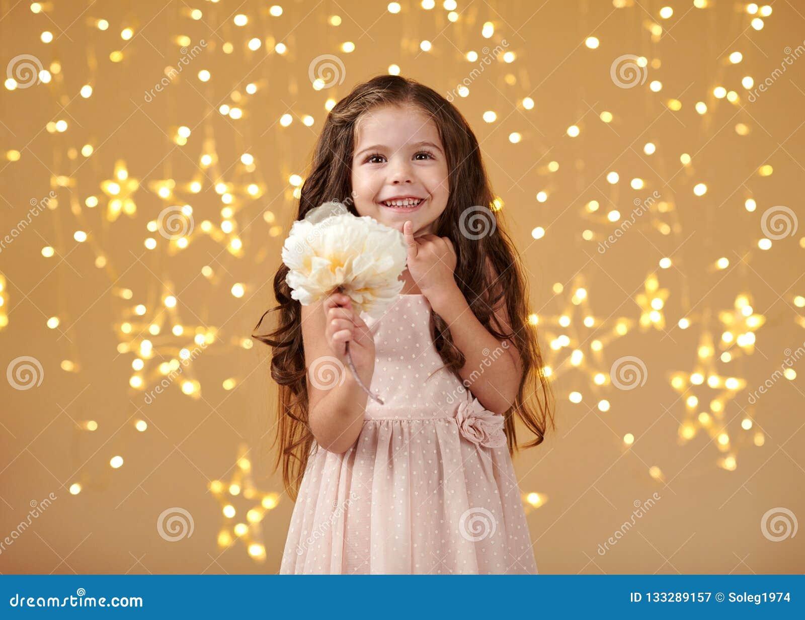 L enfant de fille est dans des lumières de Noël, fond jaune, robe rose