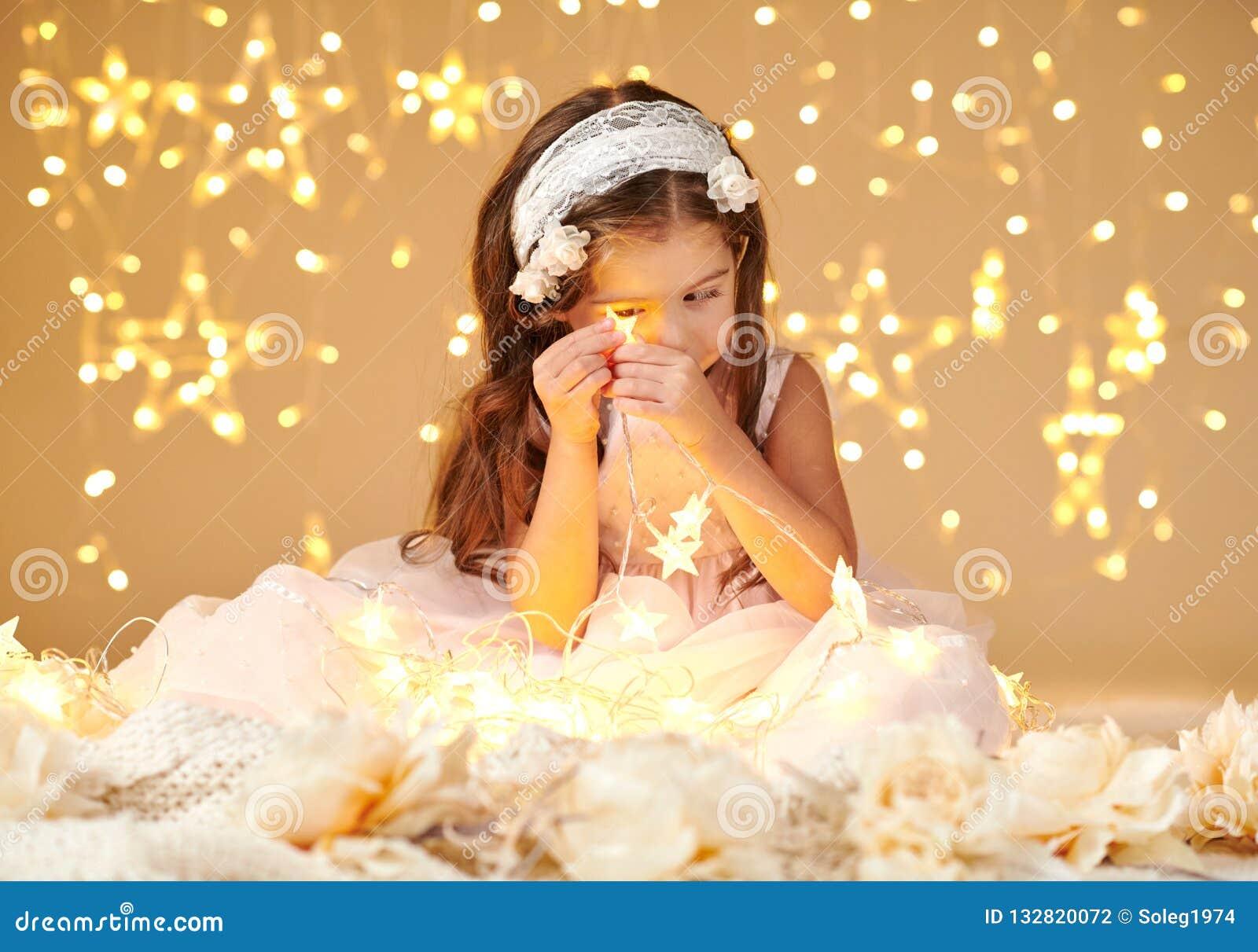 L enfant de fille joue avec des lumières de Noël, fond jaune, habillé dans la robe rose Elle regarde sur la lumière d étoile