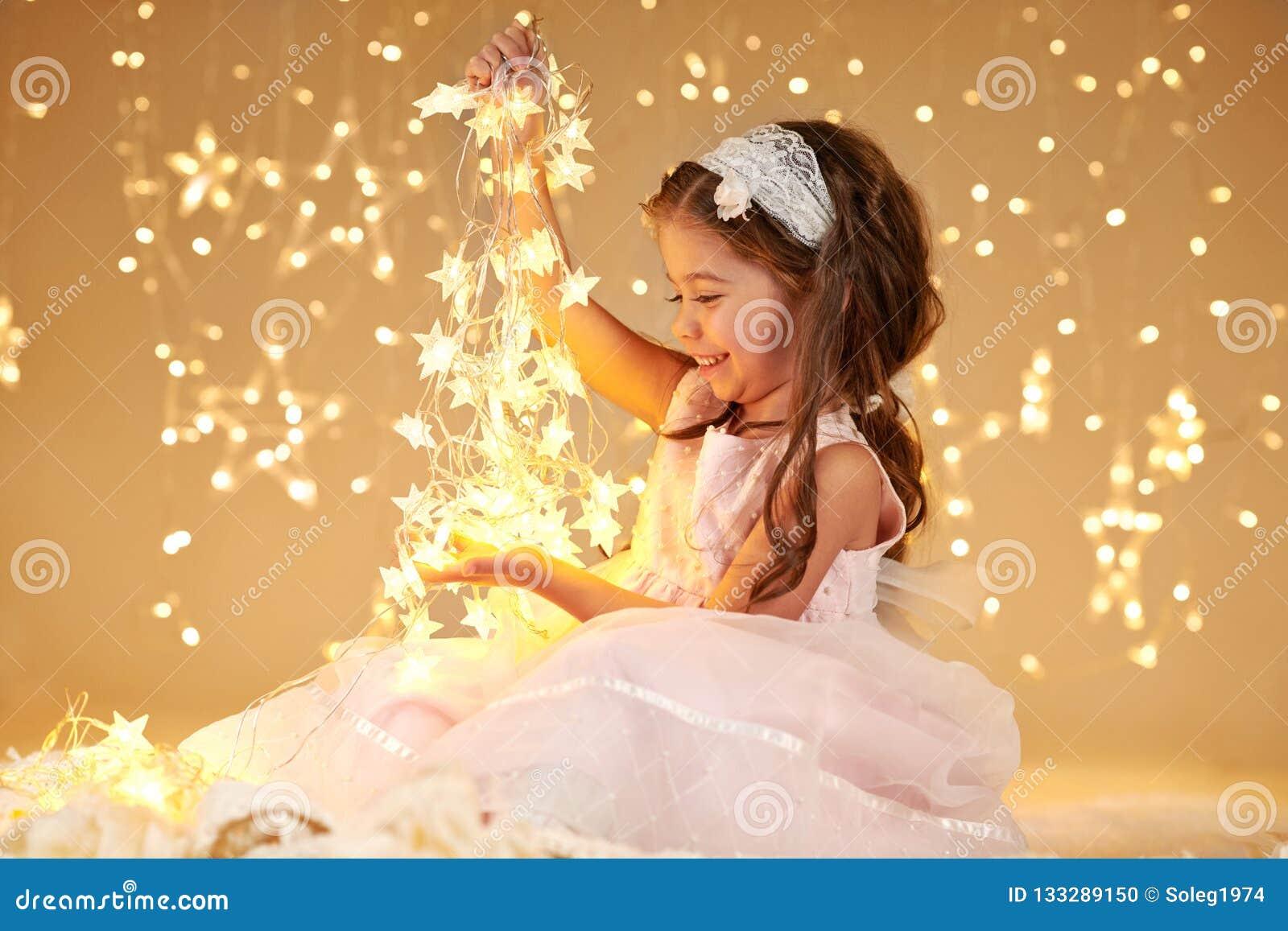 L enfant de fille joue avec des lumières de Noël, fond jaune, robe rose