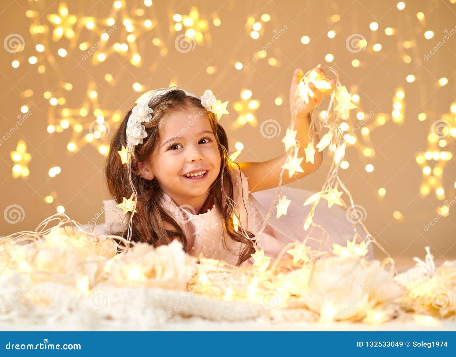 L enfant de fille pose avec des lumières de Noël, fond jaune, robe rose