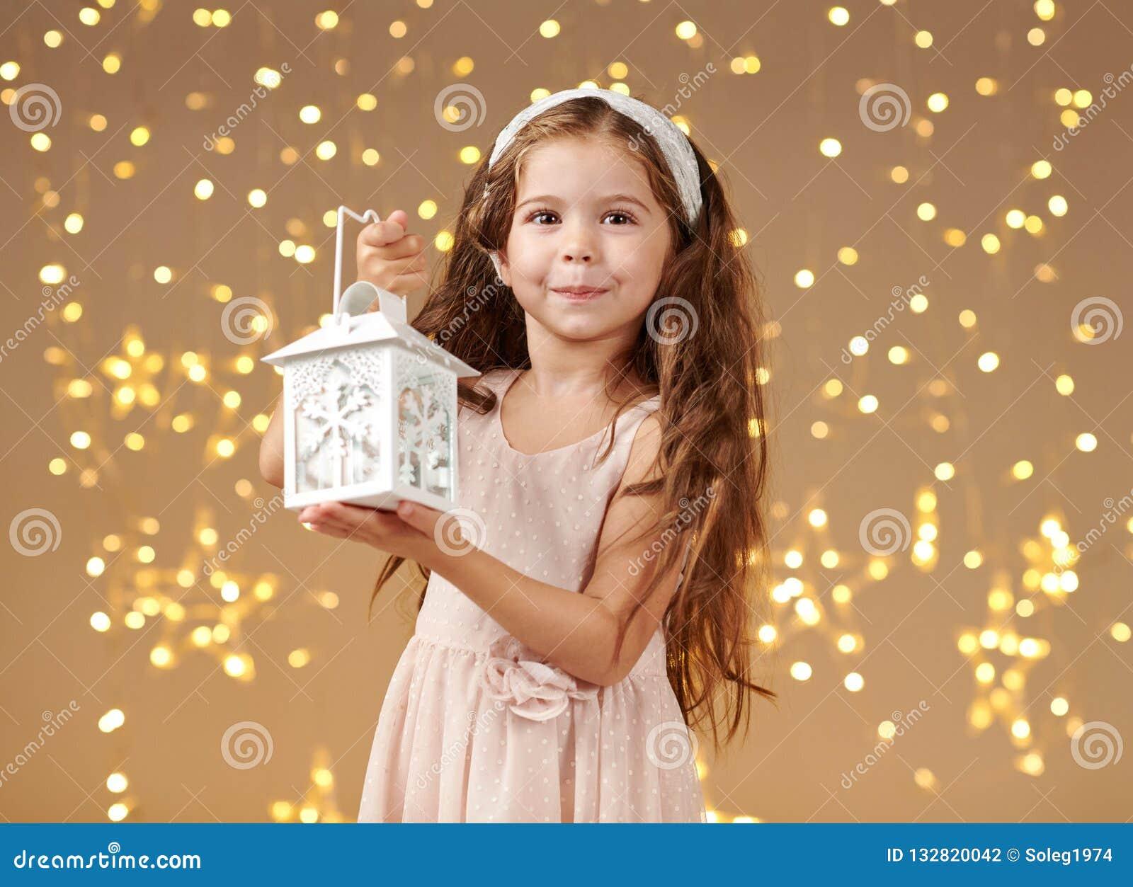 L enfant de fille pose avec la lanterne dans des lumières de Noël, fond jaune, robe rose