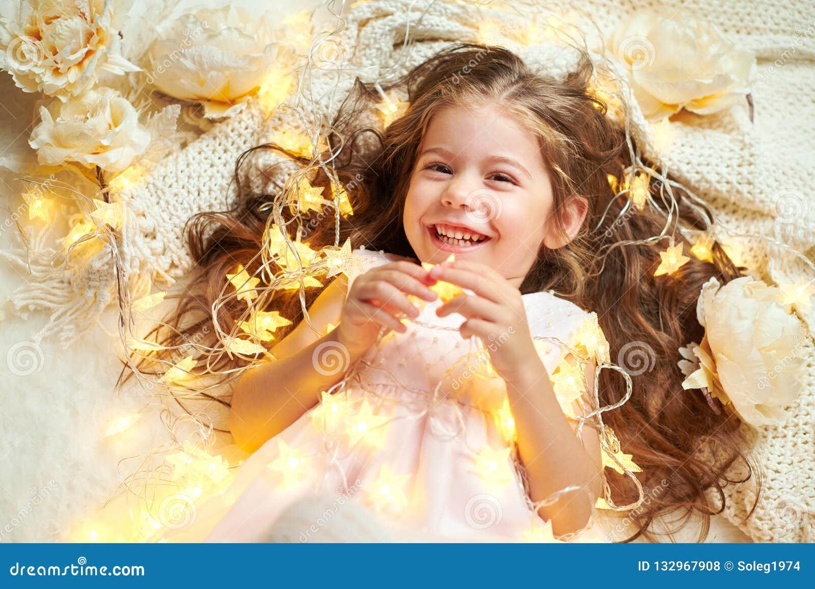 L enfant de fille se trouve avec des lumières de Noël et des fleurs, plan rapproché de visage