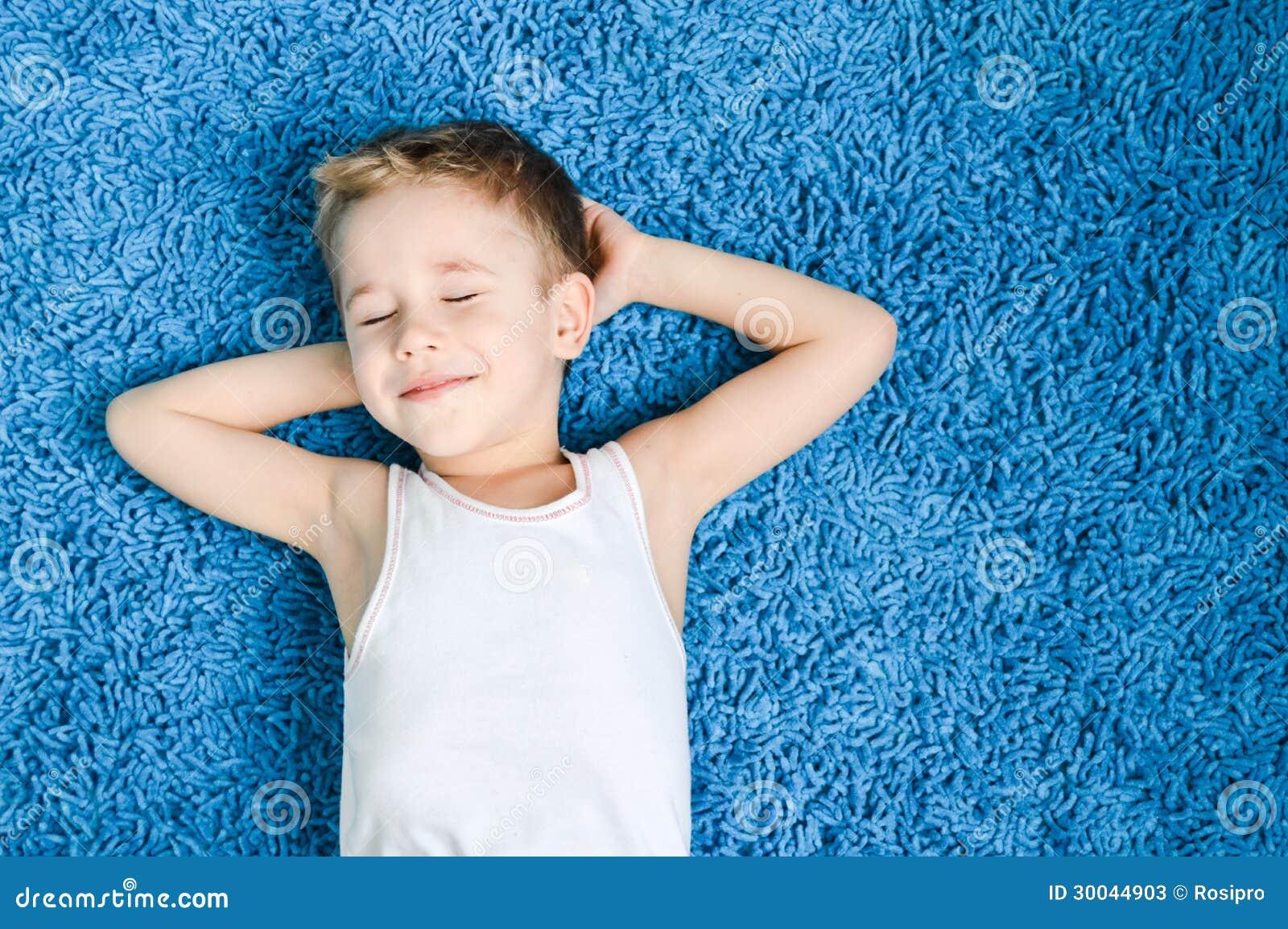 L enfant heureux sur le plancher dans le salon à la maison avec des yeux s est fermé