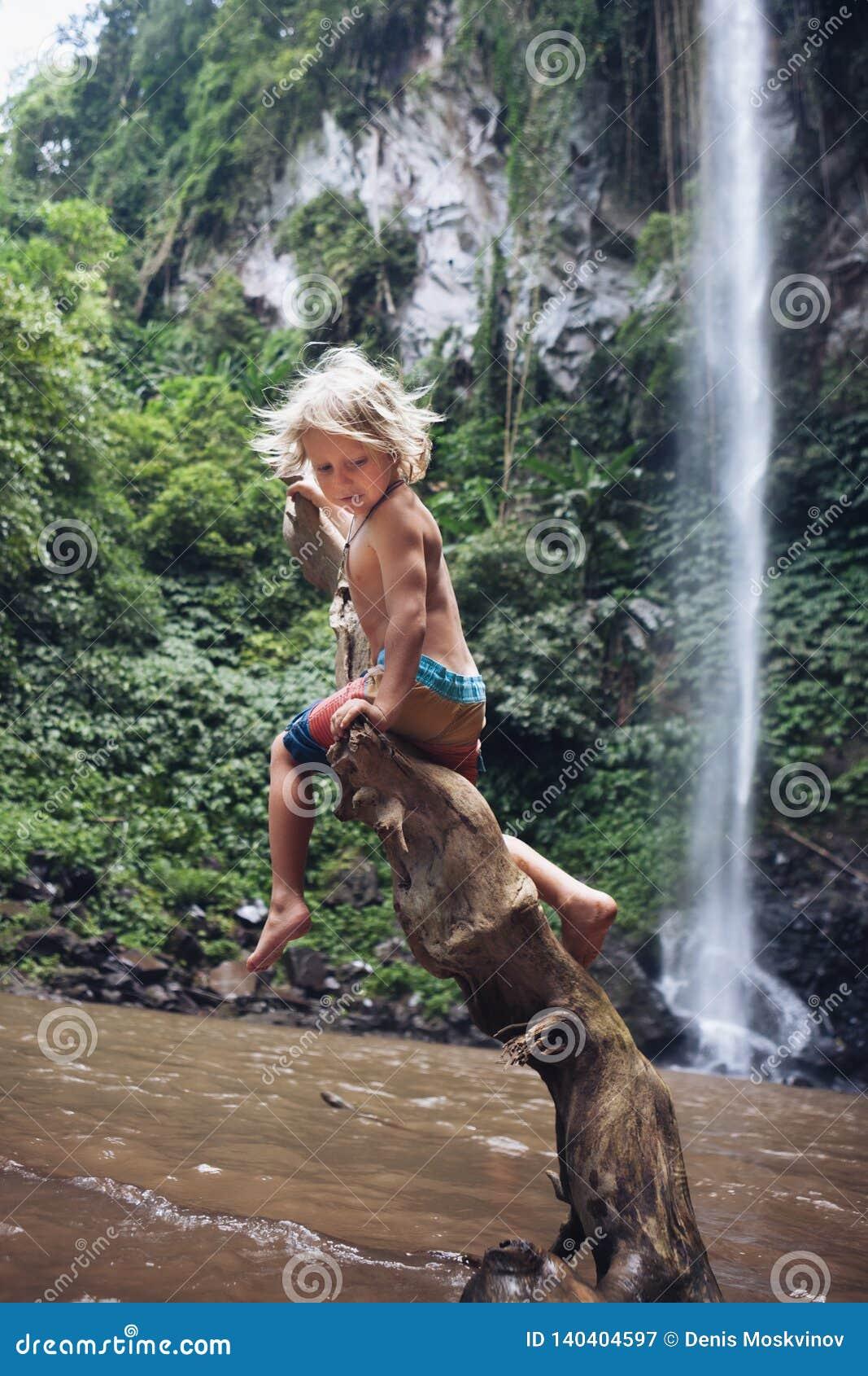 L enfant drôle s asseyent sur l accroc sous la cascade dans la jungle tropicale