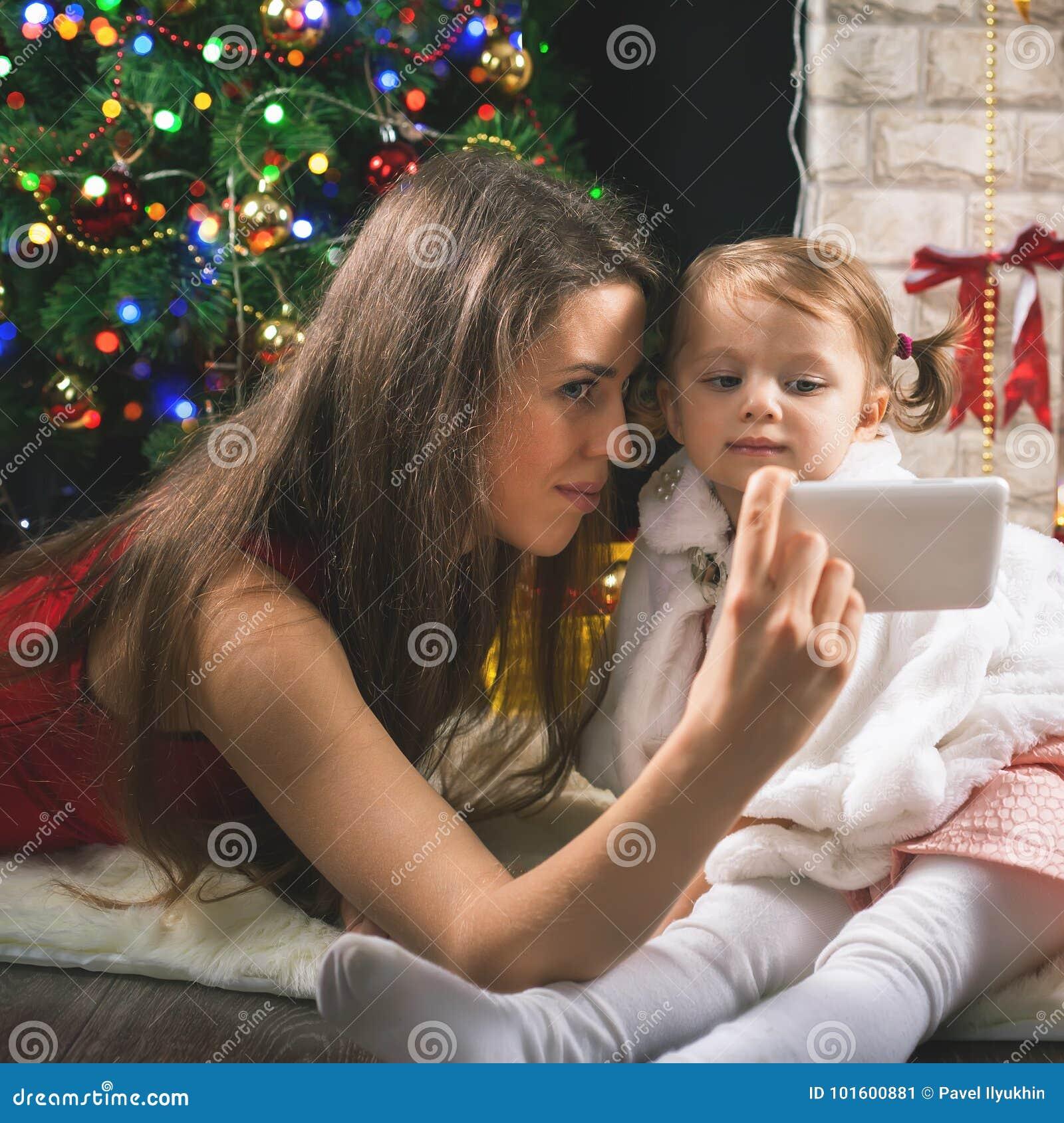 L enfant et la maman font le selfie au téléphone portable, arbre de Noël