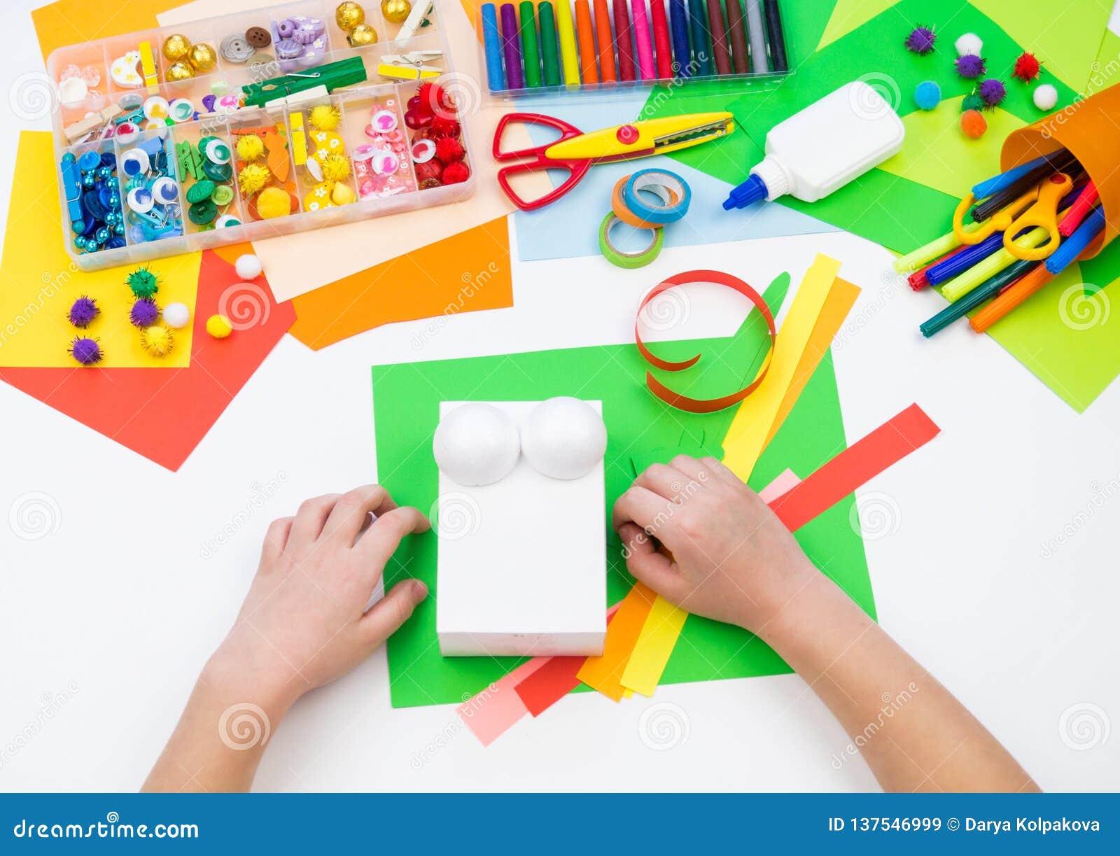 L enfant fait un caméléon de boîte d entaille Matériel pour la créativité sur un fond blanc