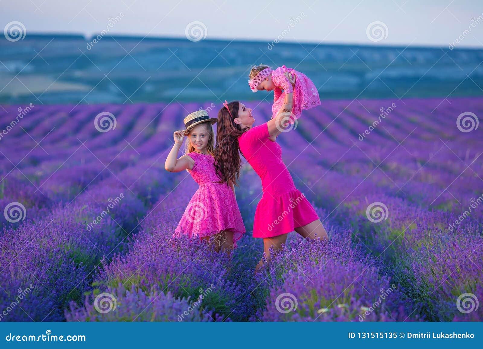 L enfant heureux de mère et de fille ainsi que les fleurs jaunes de pissenlit dans le jour d été apprécient le temps libre de vac
