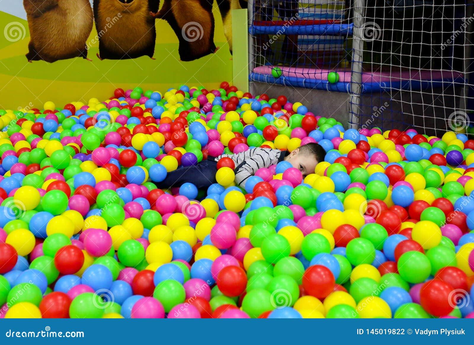 L enfant joue dans le puits de boule avec les boules en plastique color?es chez le centre de divertissement des enfants Mettez en