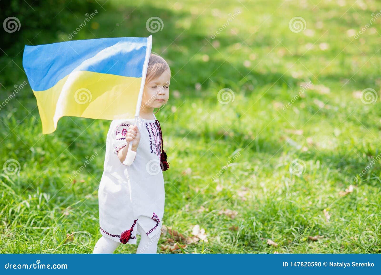 L enfant porte le flottement drapeau bleu et jaune de l Ukraine dans le domaine Jour de la D?claration d Ind?pendance du ` s de l
