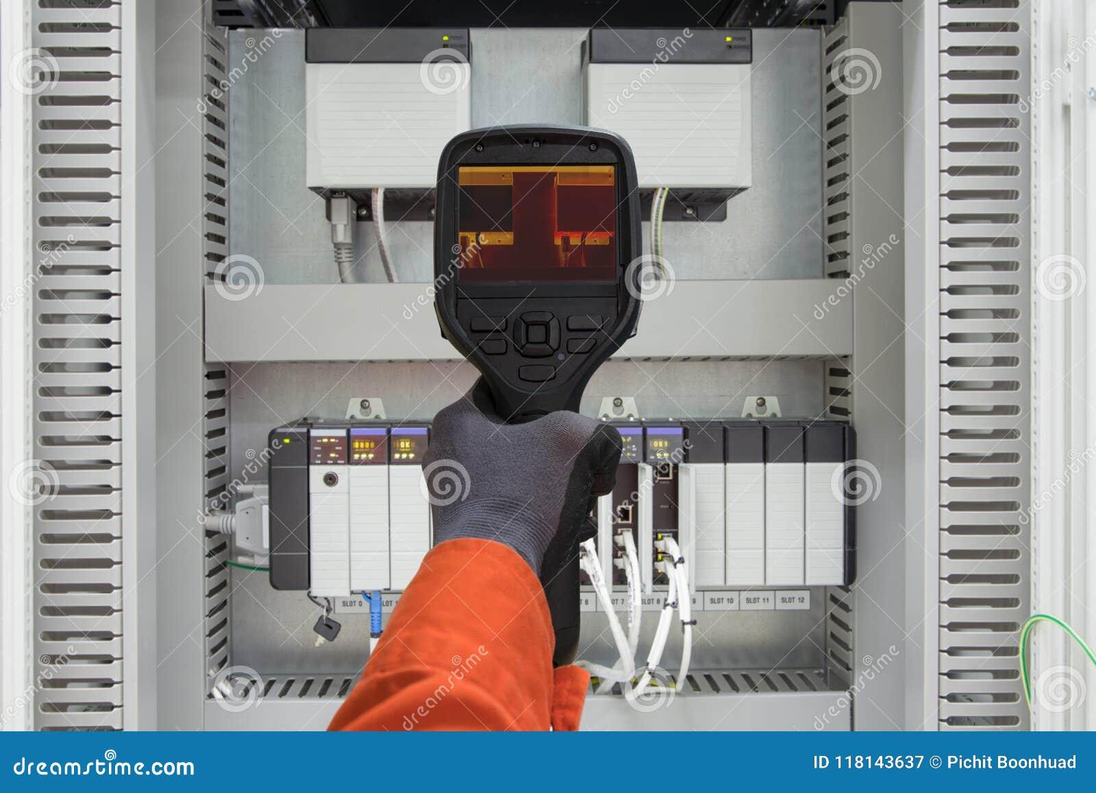 L enquête thermo d arme à feu de balayage d utilisation d électricien détendent le câble à l aide de l arme à feu de temp