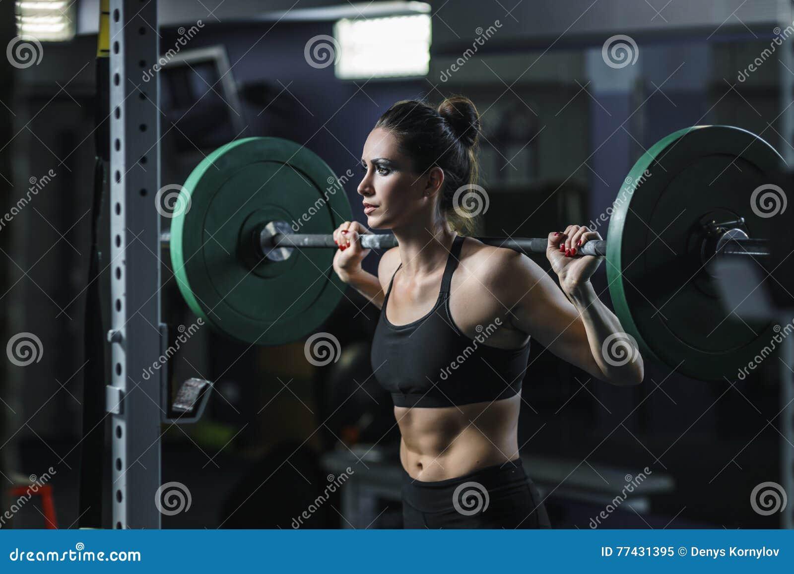 L entraîneur musculaire attirant puissant de CrossFit de femme font la séance d entraînement avec le barbell