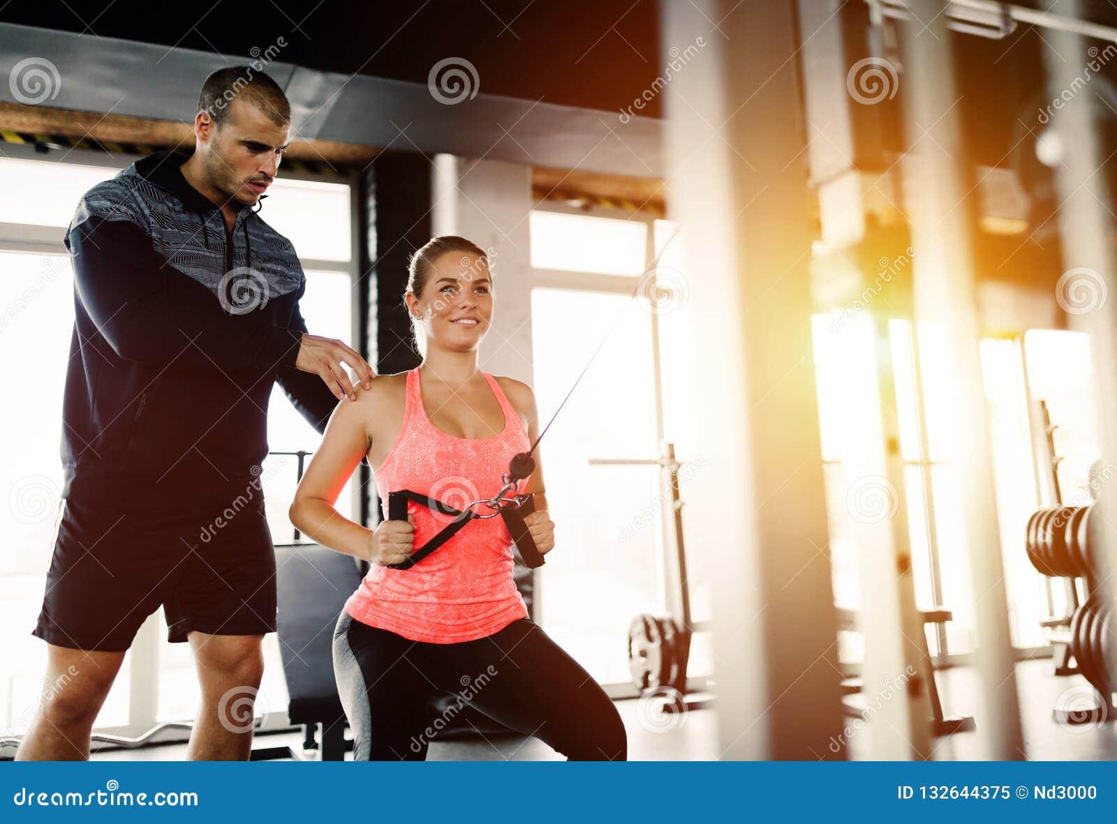 L entraîneur personnel aidant la femme perdent le poids