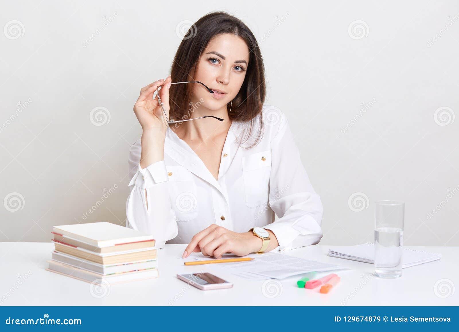 L entrepreneur assuré travaille dans la documentation d affaires, garde l eyewear près de la bouche, se prépare à la réunion d af