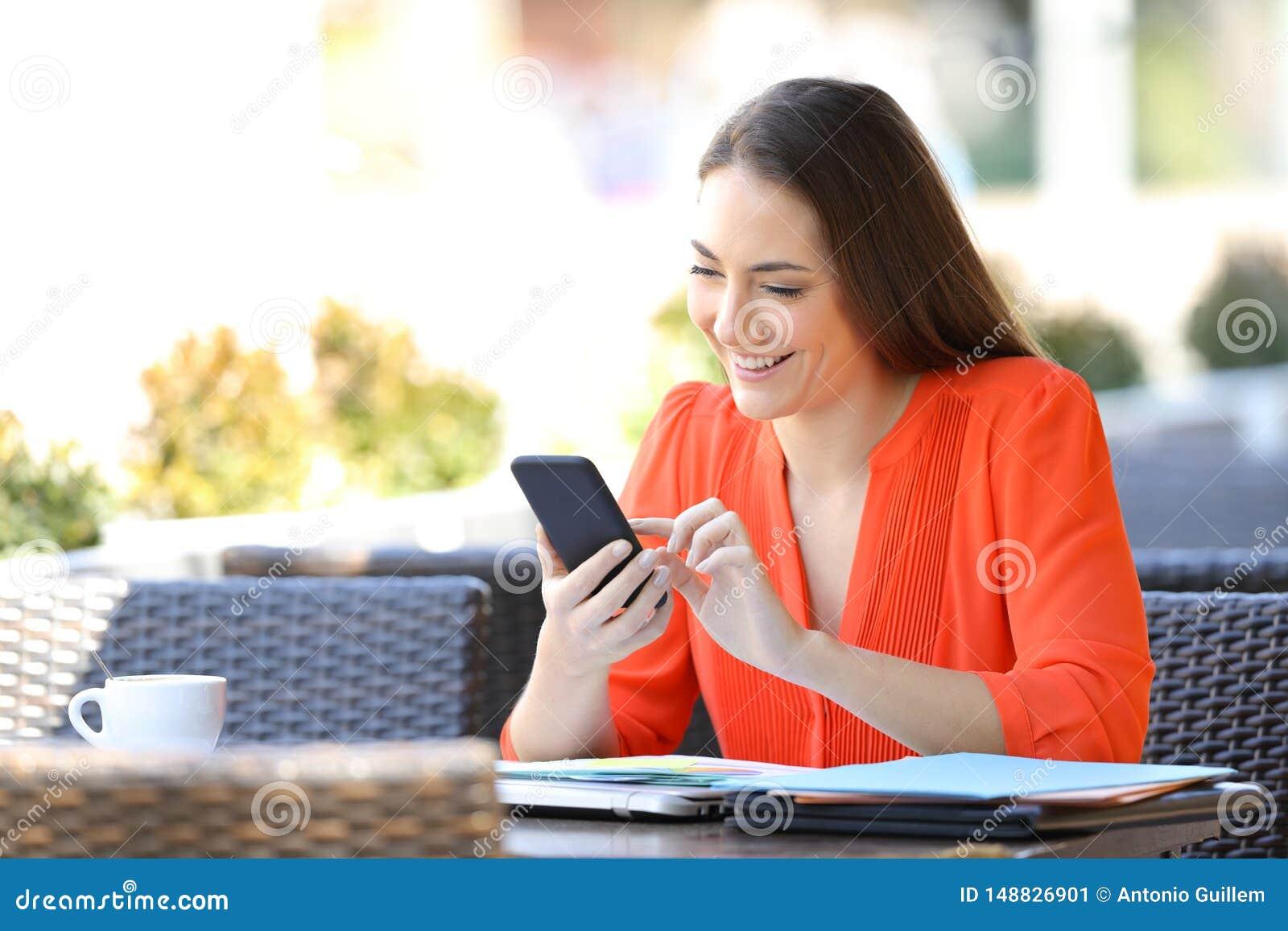 L entrepreneur heureux utilise un t?l?phone intelligent dans une terrasse de barre