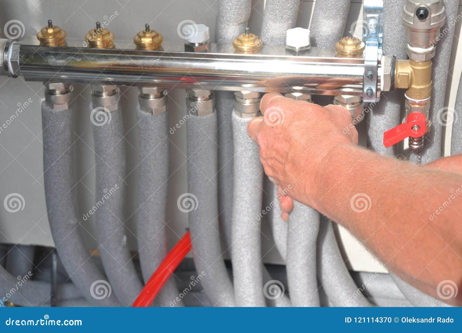 L entrepreneur installant, système de chauffage par le sol de réparation avec le métal isolé siffle