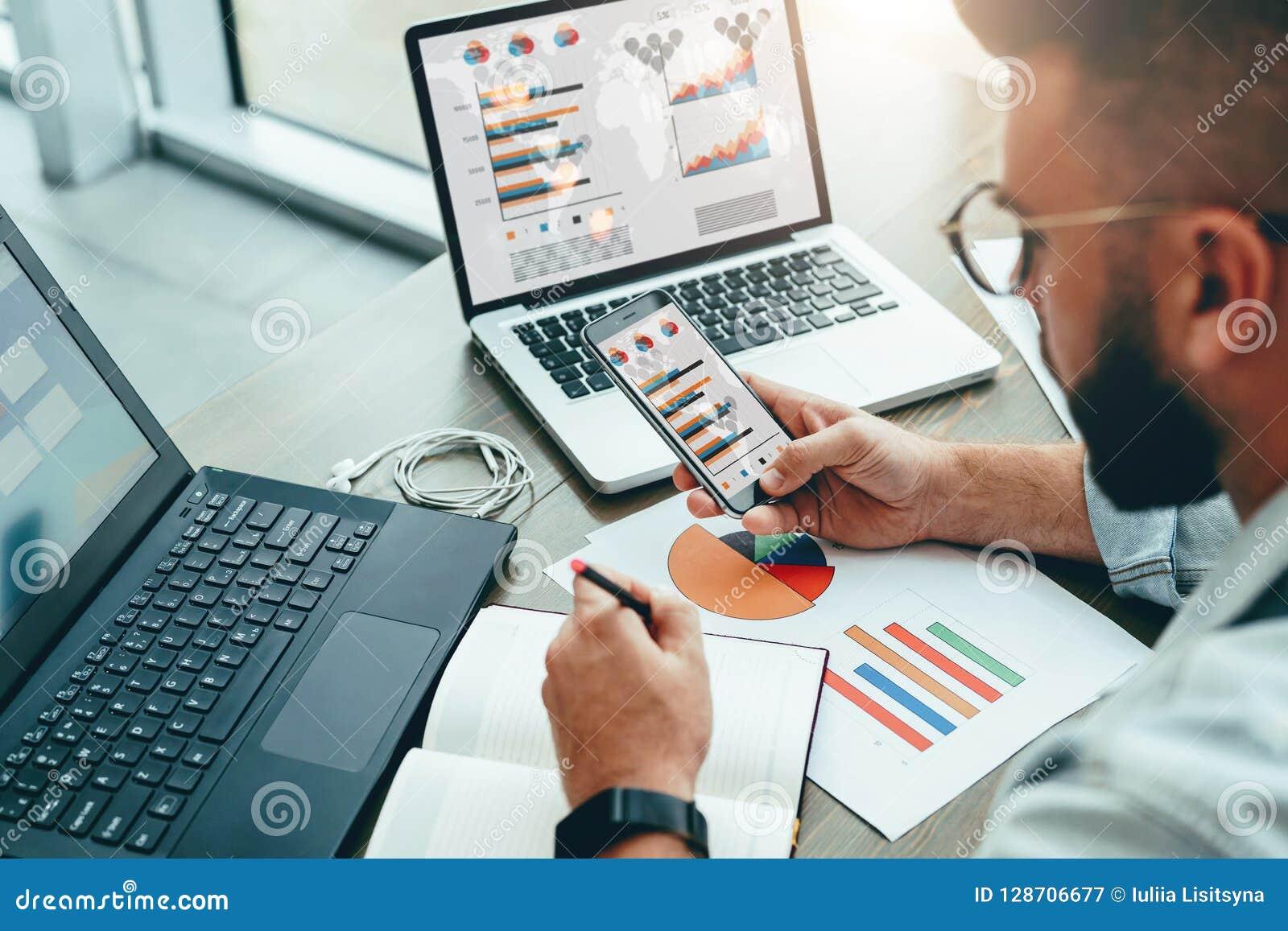 L entrepreneur s assied dans le bureau, utilise le smartphone, travaillant sur l ordinateur portable avec des diagrammes, des dia