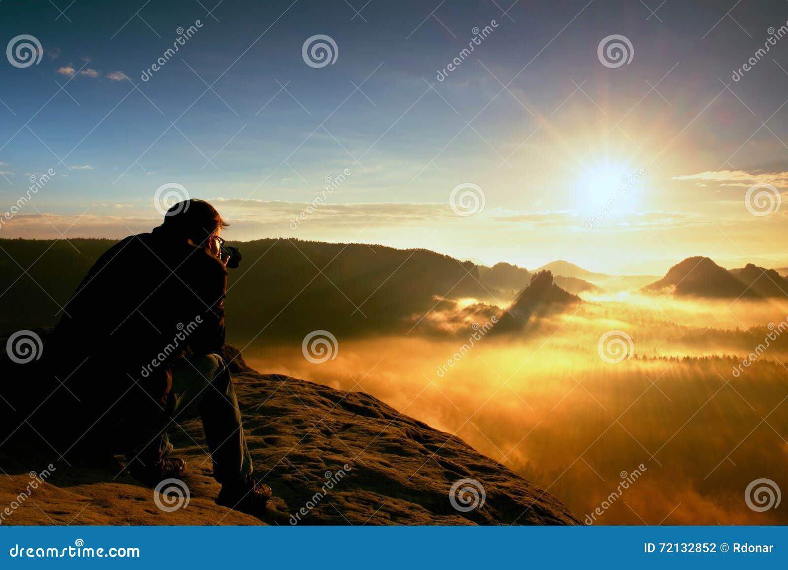 L entusiasta felice della foto sta godendo del miracolo fantastico della natura sulla scogliera su roccia Muggito vago del paesag