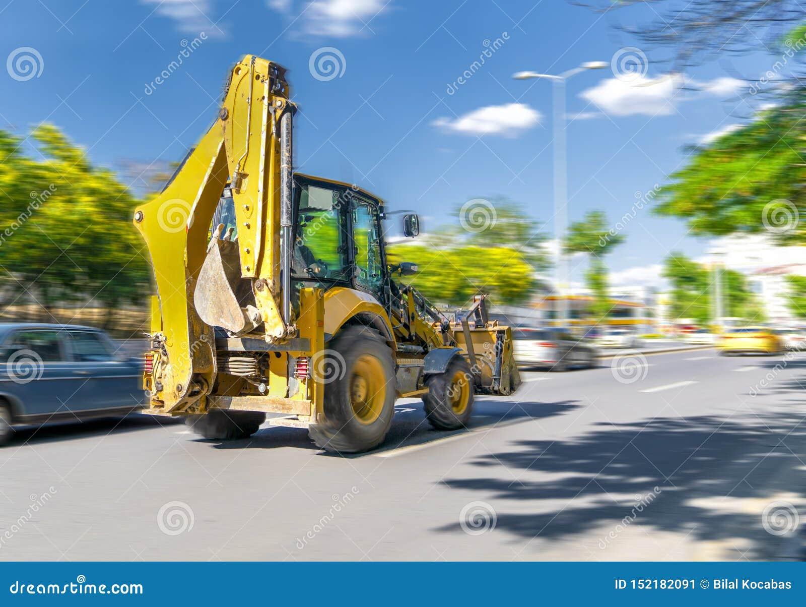 L escavatore guida o va velocemente sulla via con traffico pesante con cielo blu e gli alberi verdi nel fondo, Ankara, Turchia