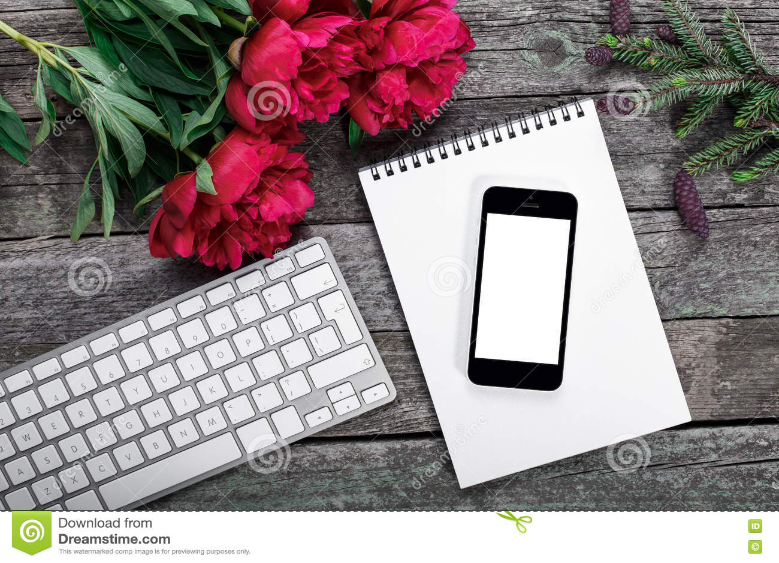 L espace de travail avec le smartphone, le clavier, le bloc-notes, la branche de sapin et les pivoines fleurit le bouquet sur le