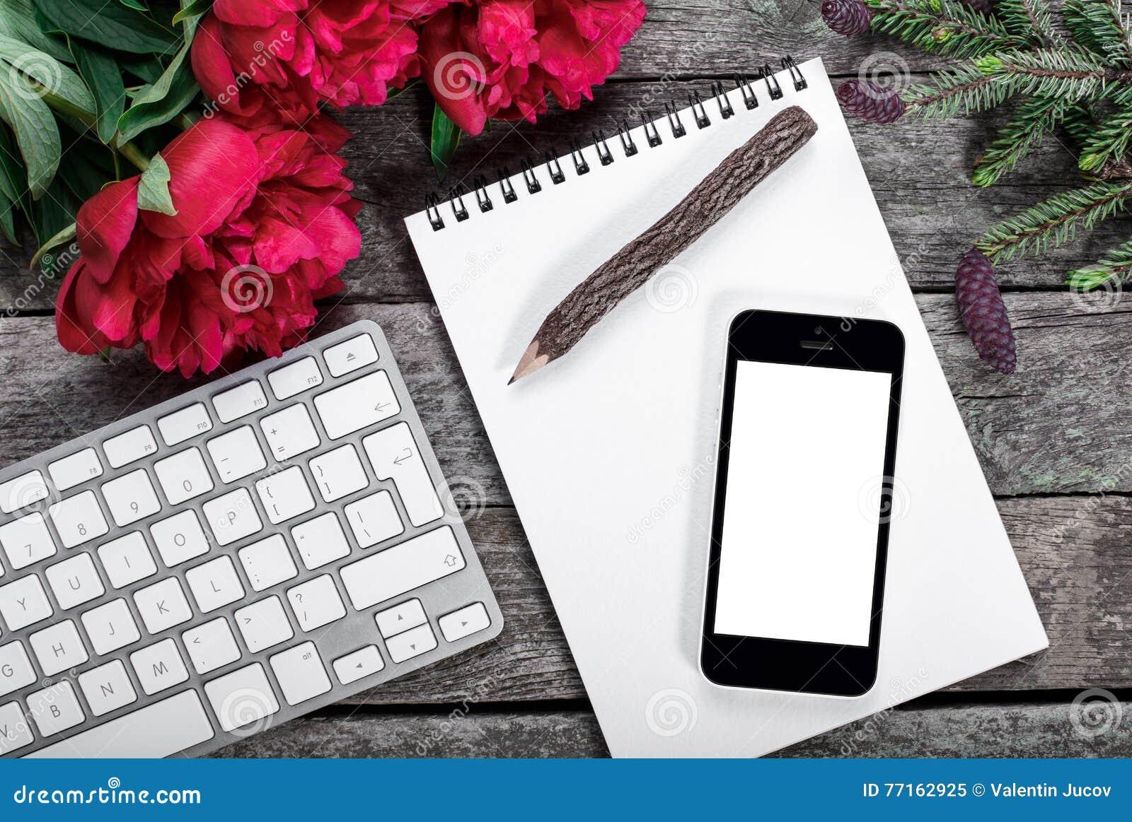 L espace de travail avec le smartphone, le clavier, le bloc-notes, le crayon en bois, la branche de sapin et les pivoines fleurit