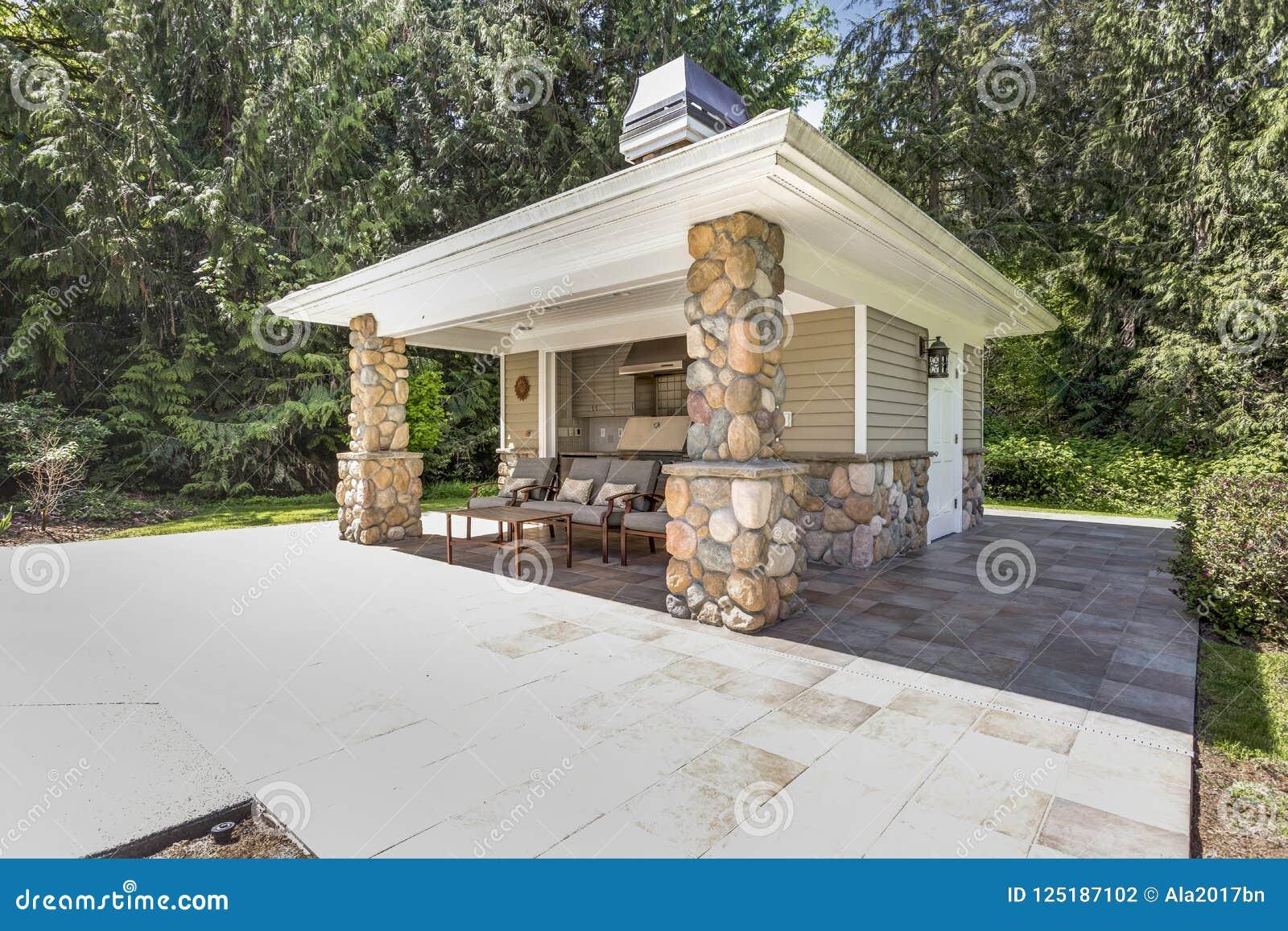 L espace extérieur chic de cuisine avec les colonnes en pierre