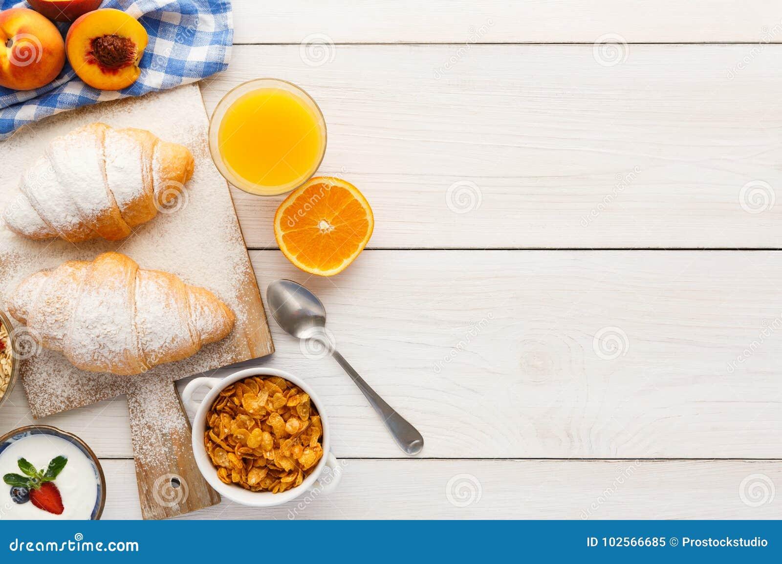 Fond français traditionnel de menu de petit déjeuner Yaourt avec les baies  fraîches, le verre de jus d orange, le muesli et les croissants sur la  table en ... 20b7c65f3754