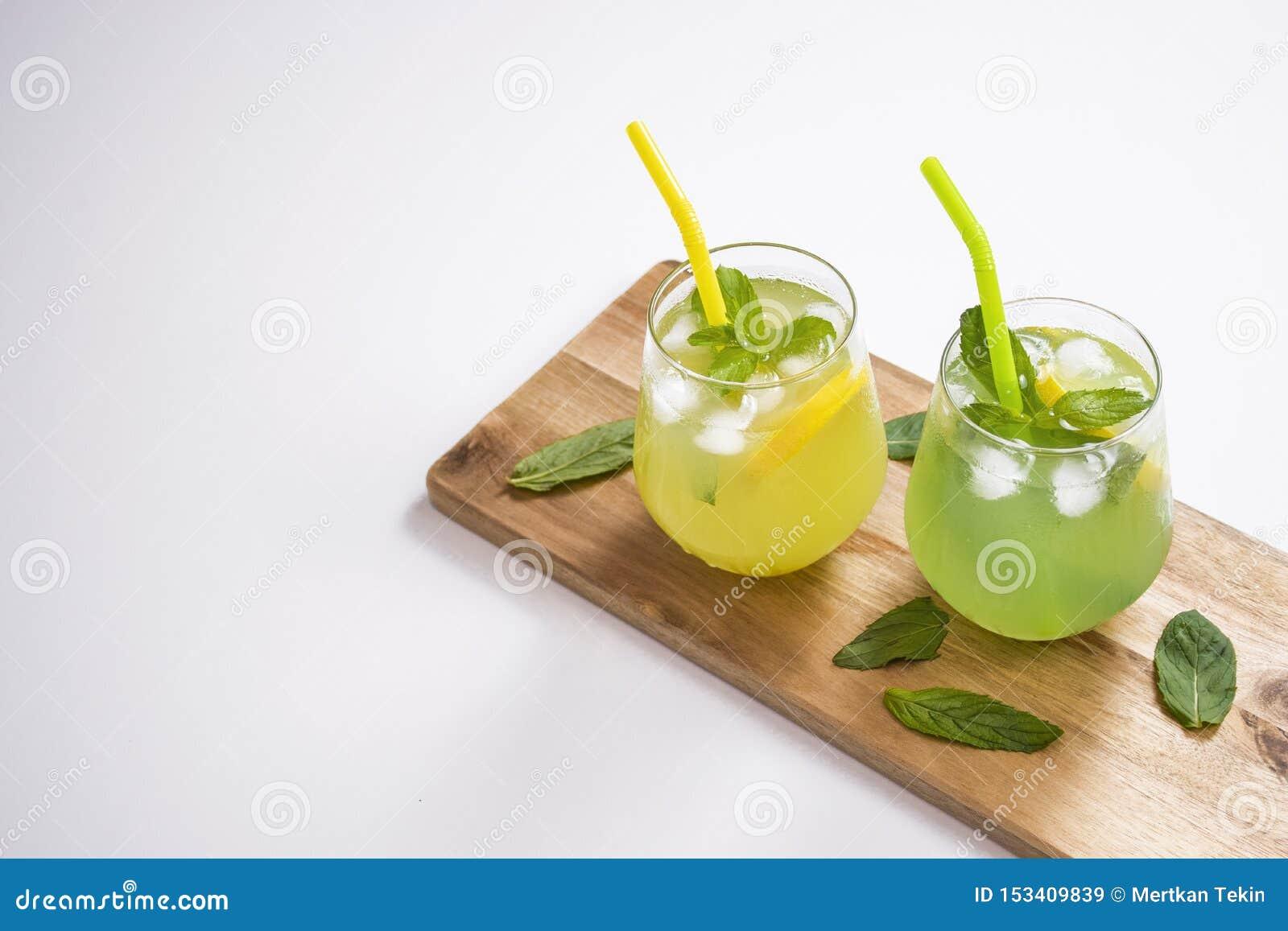 L estate beve il mojito della limonata con ghiaccio e la menta su fondo isolato