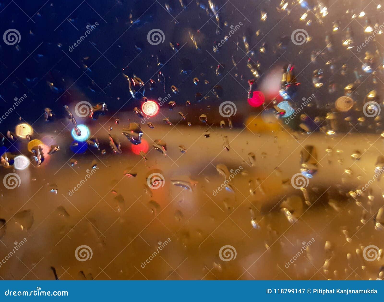 L estratto vago del vetro di finestra bagnato con le gocce di pioggia e lo scintillio del bokeh accende il fondo il giorno piovos