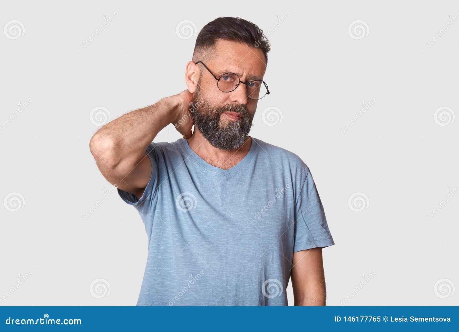 L exécutif bel impassible fatigué regarde fermement la caméra, tenant son bras derrière, faisant le massage de cou après jour ouv