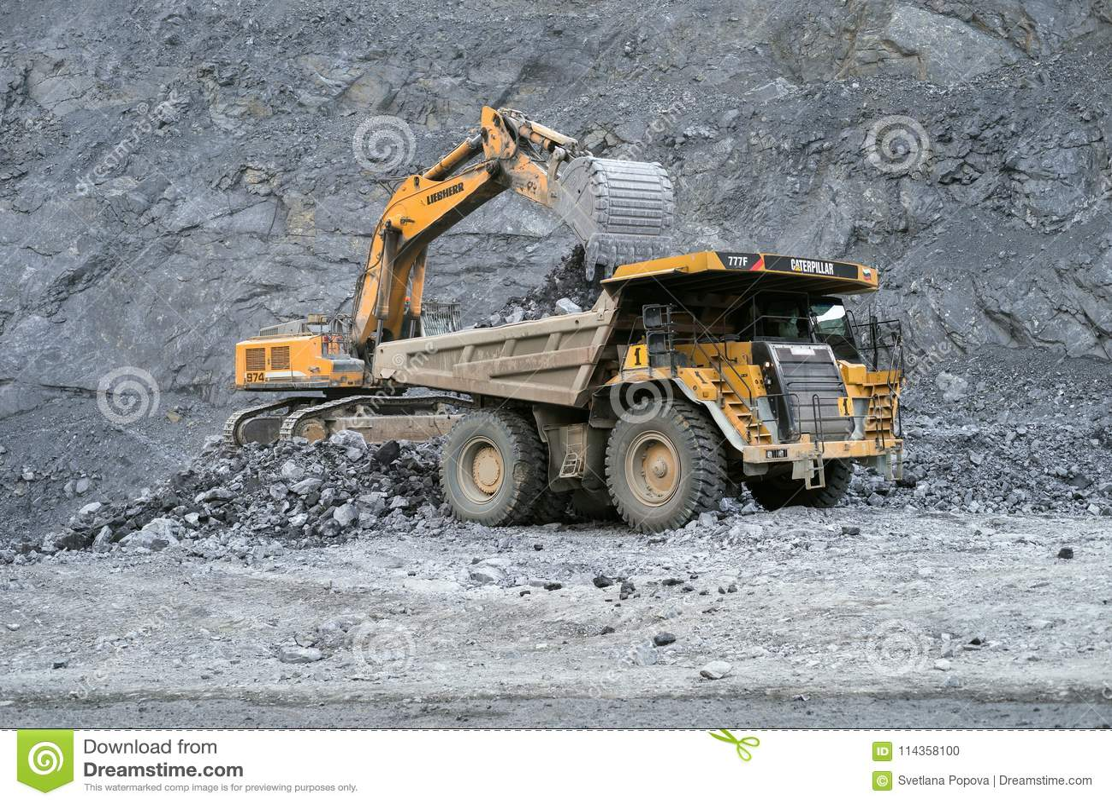 L excavatrice Liebherr charge le minerai dans un camion à benne basculante Caterpillar à l arrière-plan d une carrière
