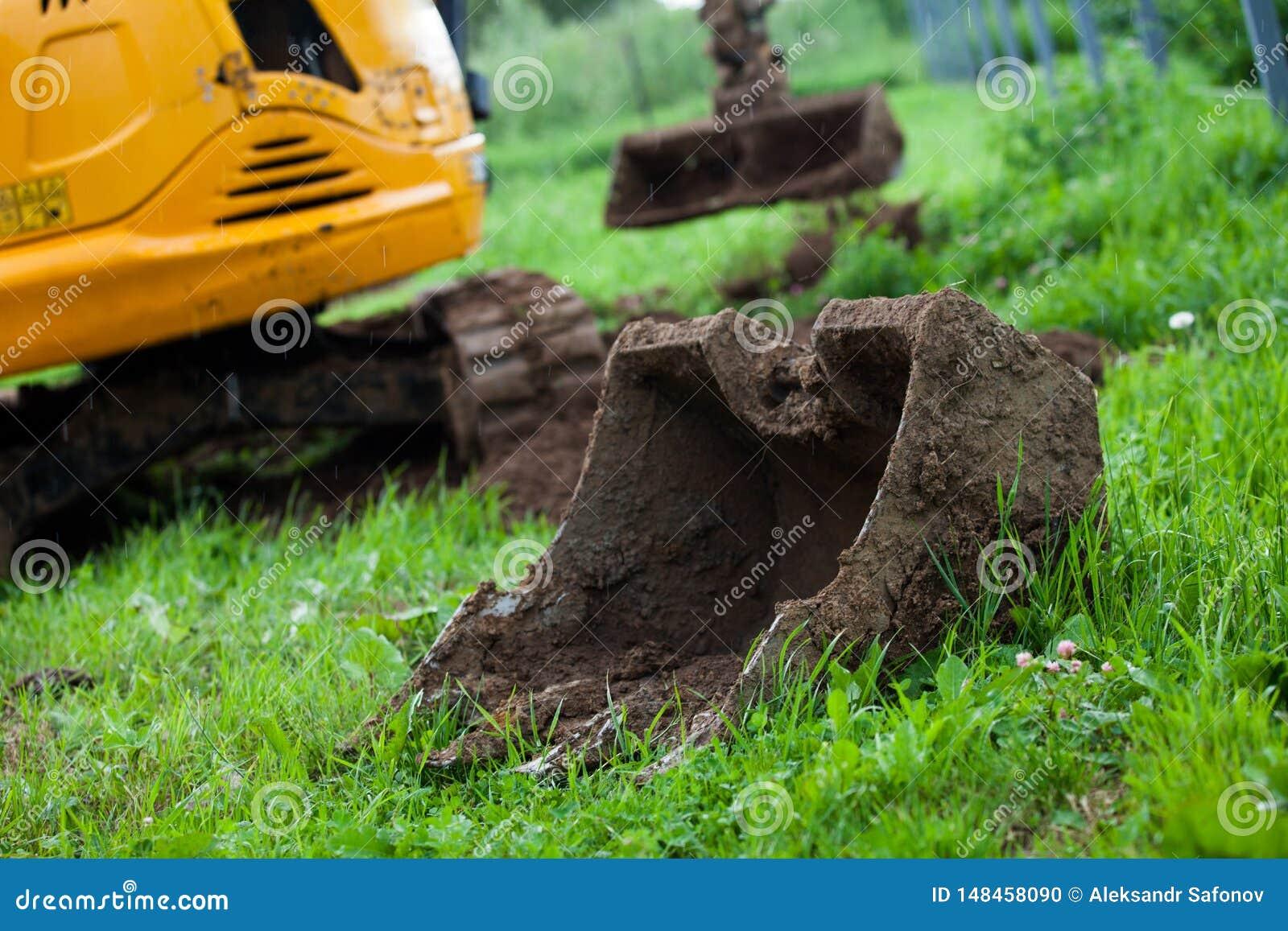 L excavatrice nivelle la terre sur le site