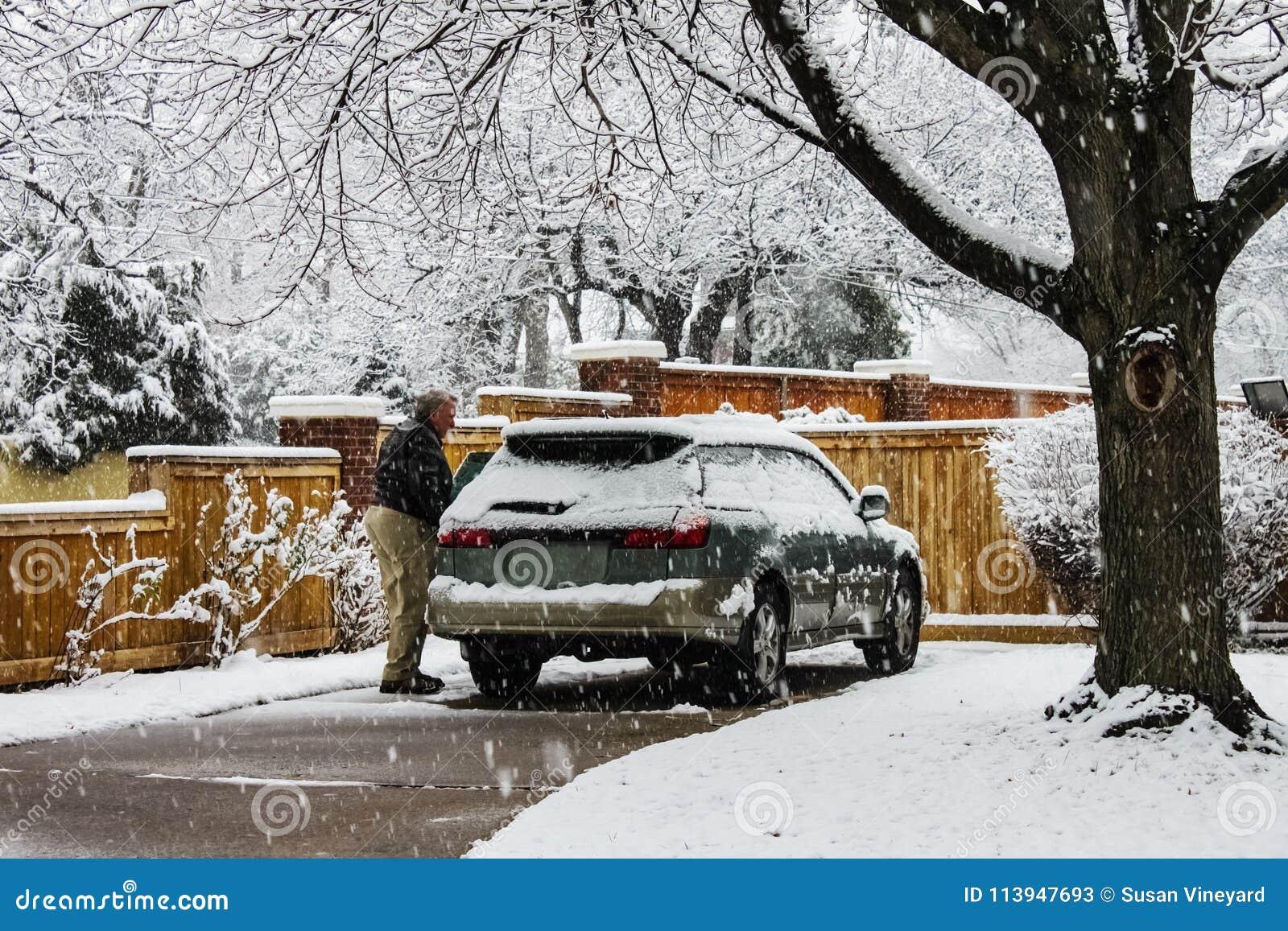L homme âgé par milieu avec la neige a couvert la voiture dans l allée le jour extrêmement neigeux de chute de neige