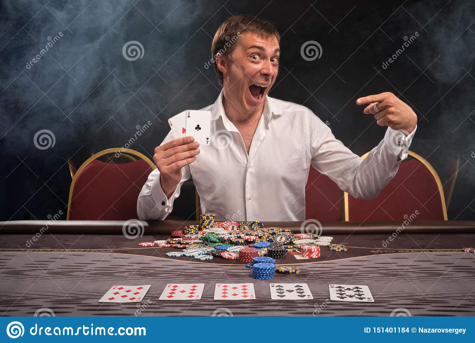 L homme émotif bel joue au poker se reposant à la table dans le casino