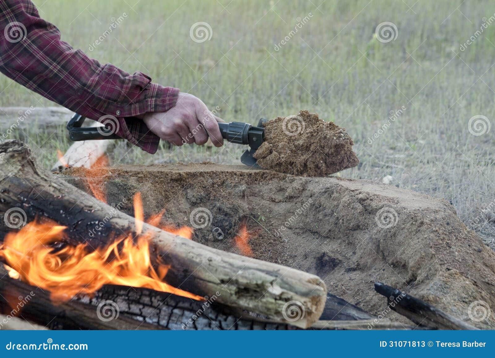 L homme établit le feu Pit Around Open Camp Fire