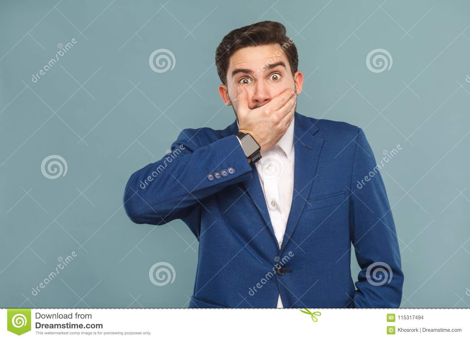 L homme étonné avec de grands yeux a fermé la bouche de mains