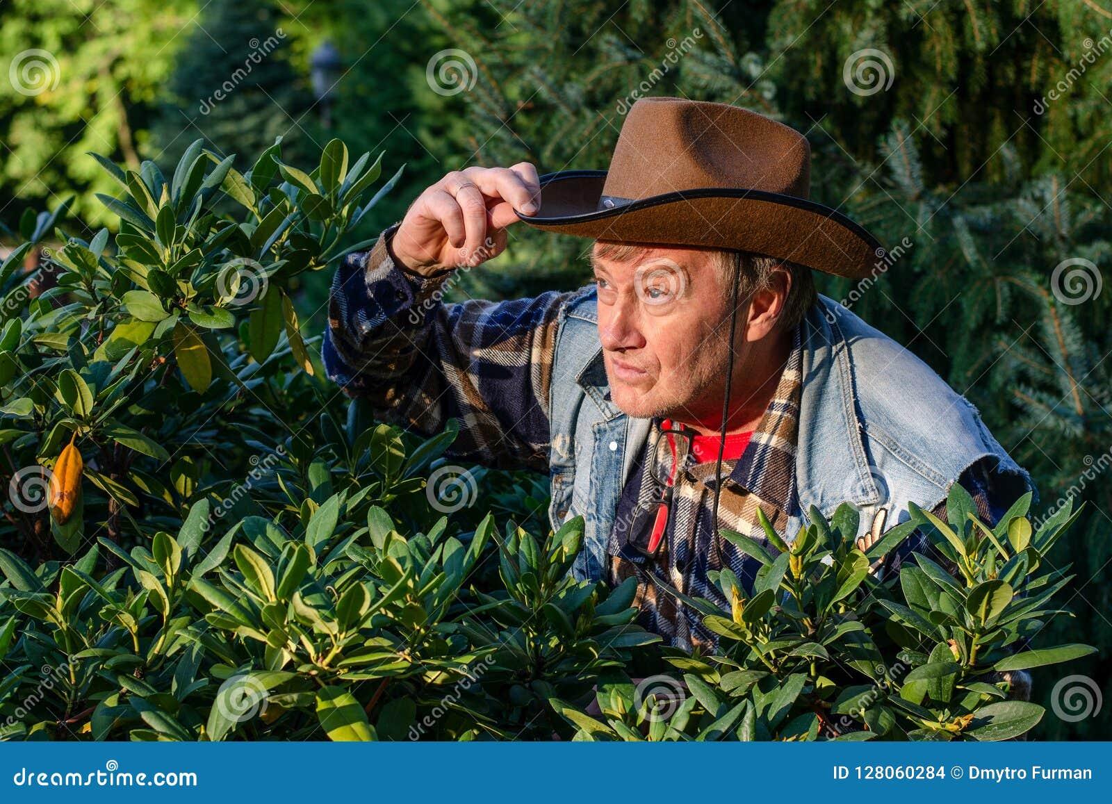 L homme adulte supérieur ou un agriculteur, dans un chapeau de cowboy brun, regarde o