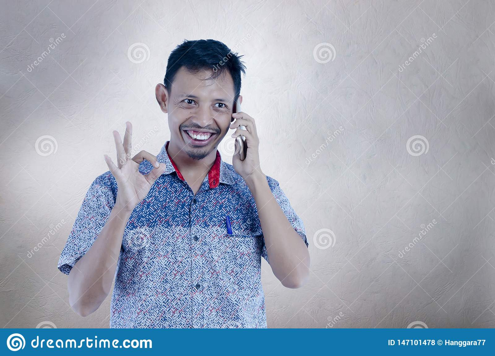 L homme asiatique parlant au téléphone au-dessus du fond gris d isolement faisant le signe d ok avec des doigts, faire positif de