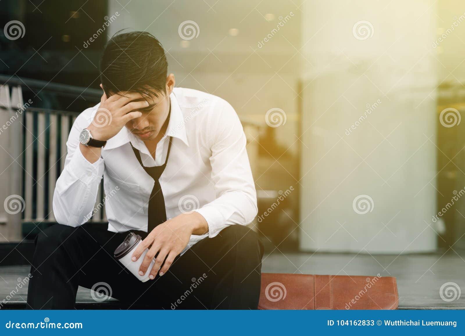 L homme asiatique s assied sur les étapes d un immeuble de bureaux avec l effort