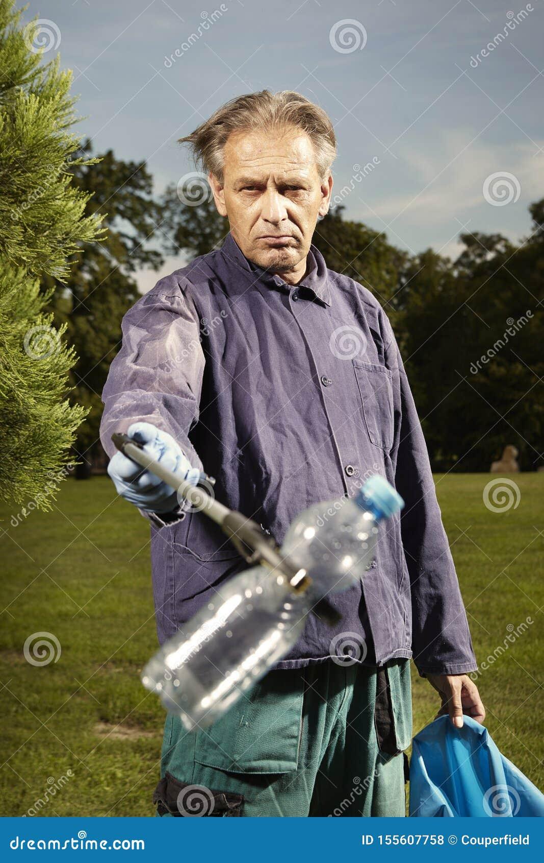 L homme au travail prennent des déchets sur l herbe en parc