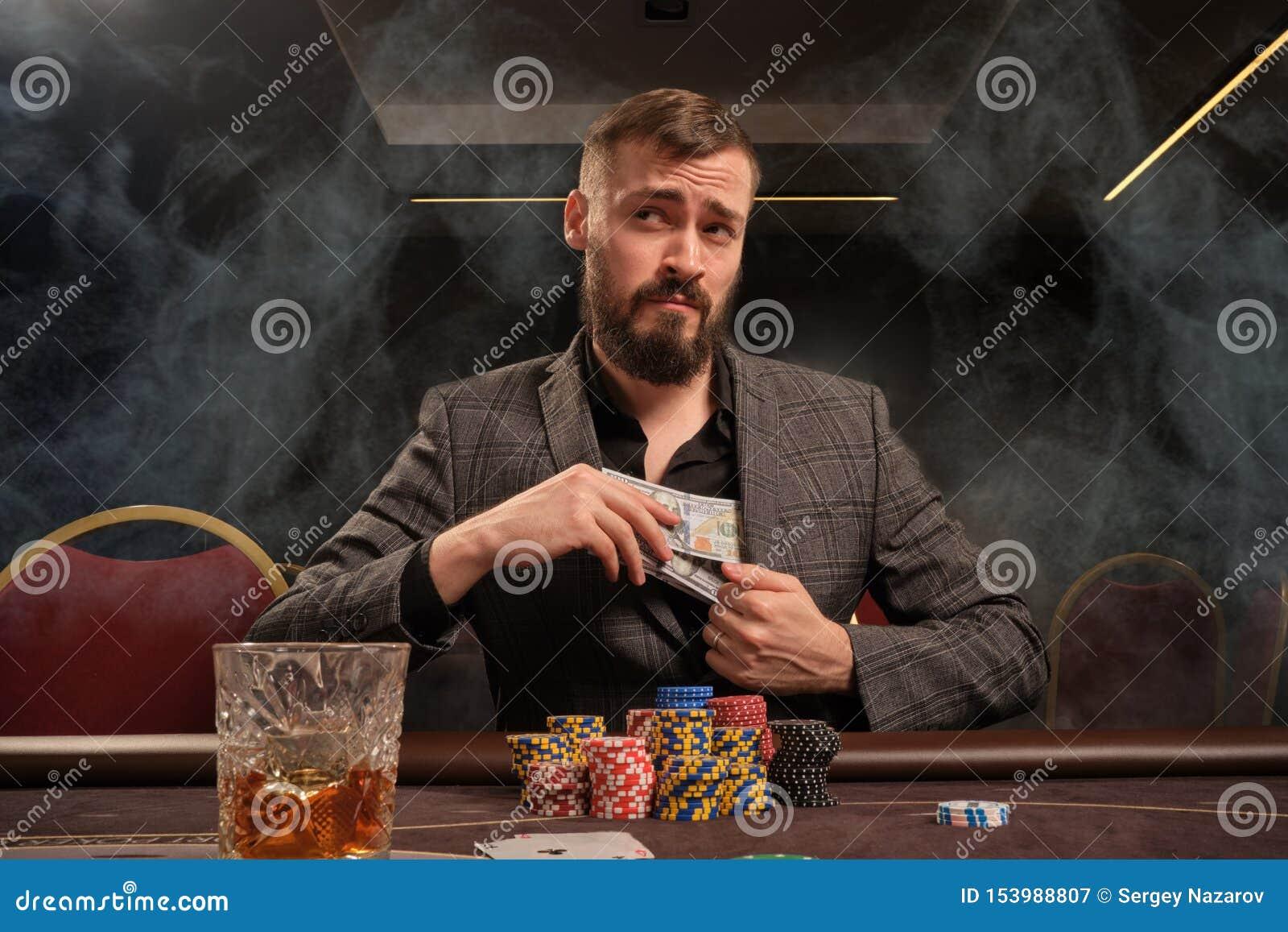 L homme barbu bel joue au poker se reposant à la table dans le casino