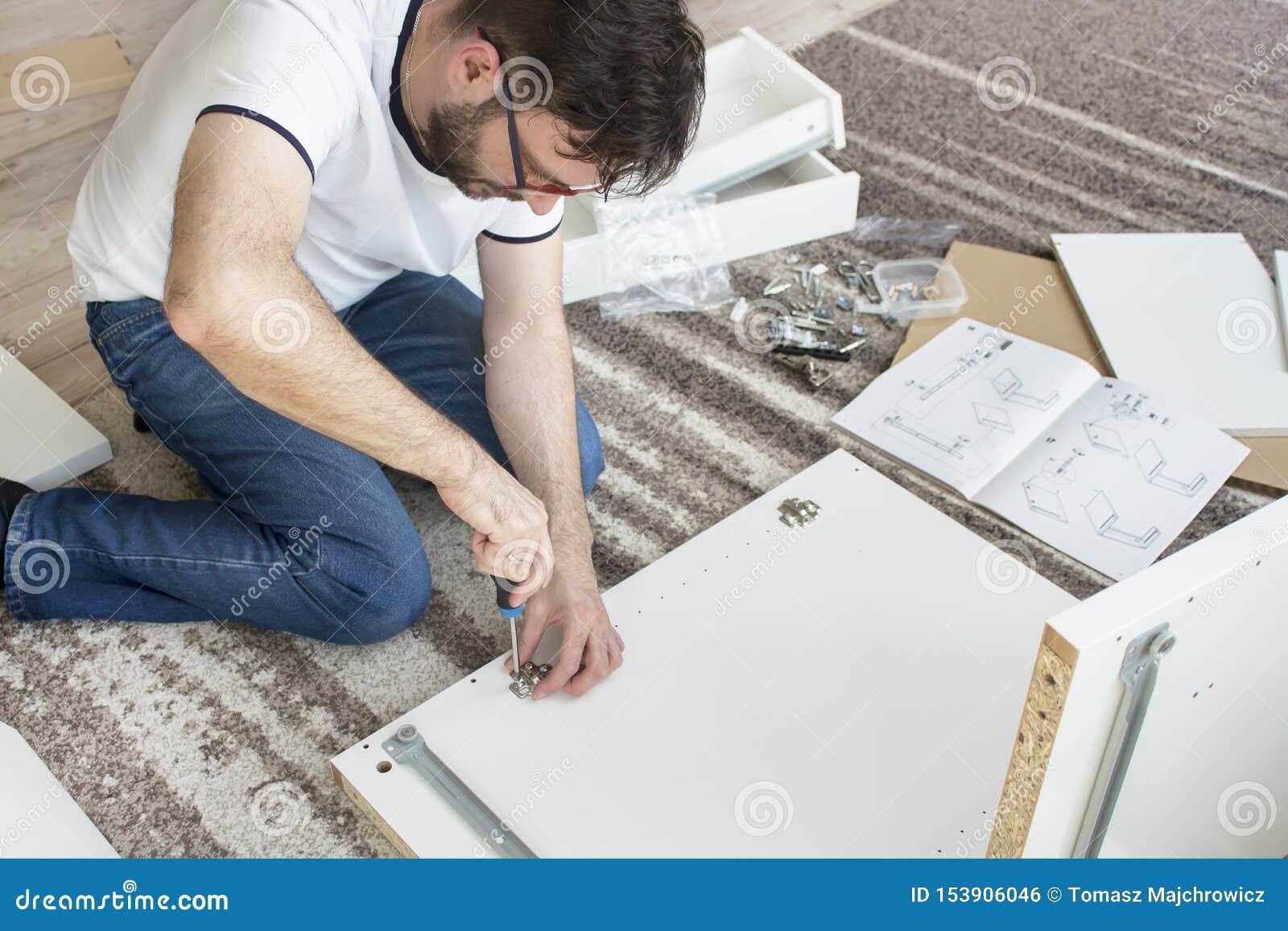 L homme barbu dans les verres, un T-shirt blanc et des jeans s assied sur un tapis dans le salon et les meubles de torsions Il ti
