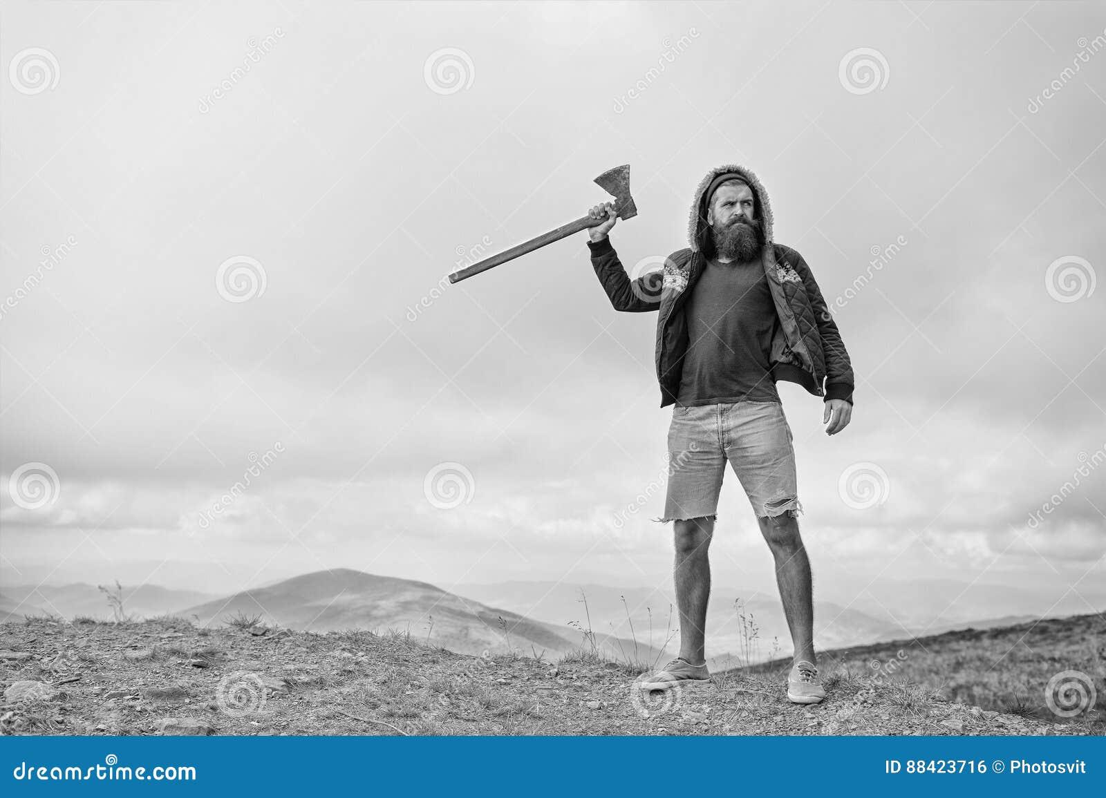 L homme barbu, hippie brutal avec la moustache tient la hache sur la montagne