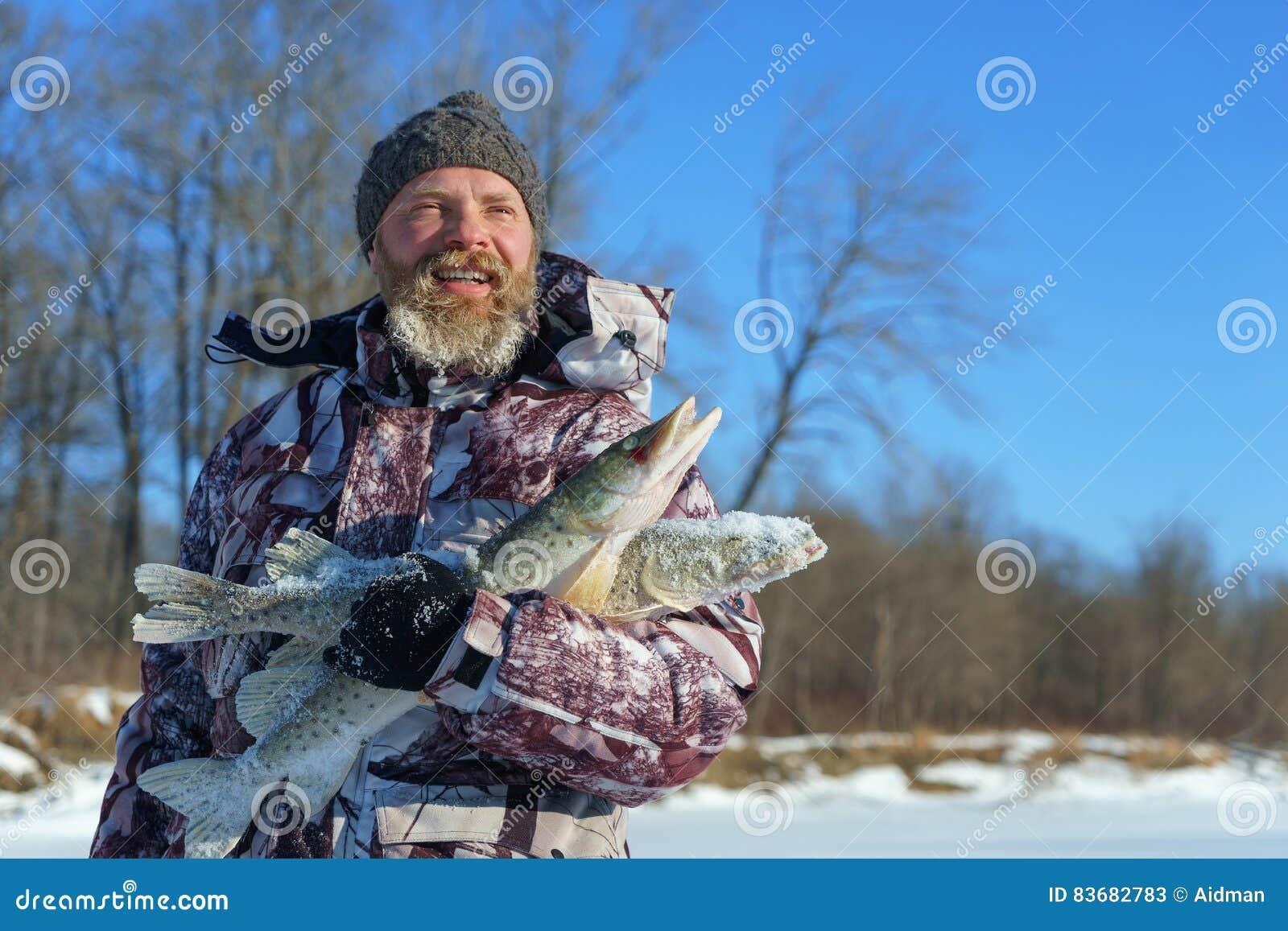L homme barbu tient les poissons congelés après la pêche réussie d hiver au jour ensoleillé froid