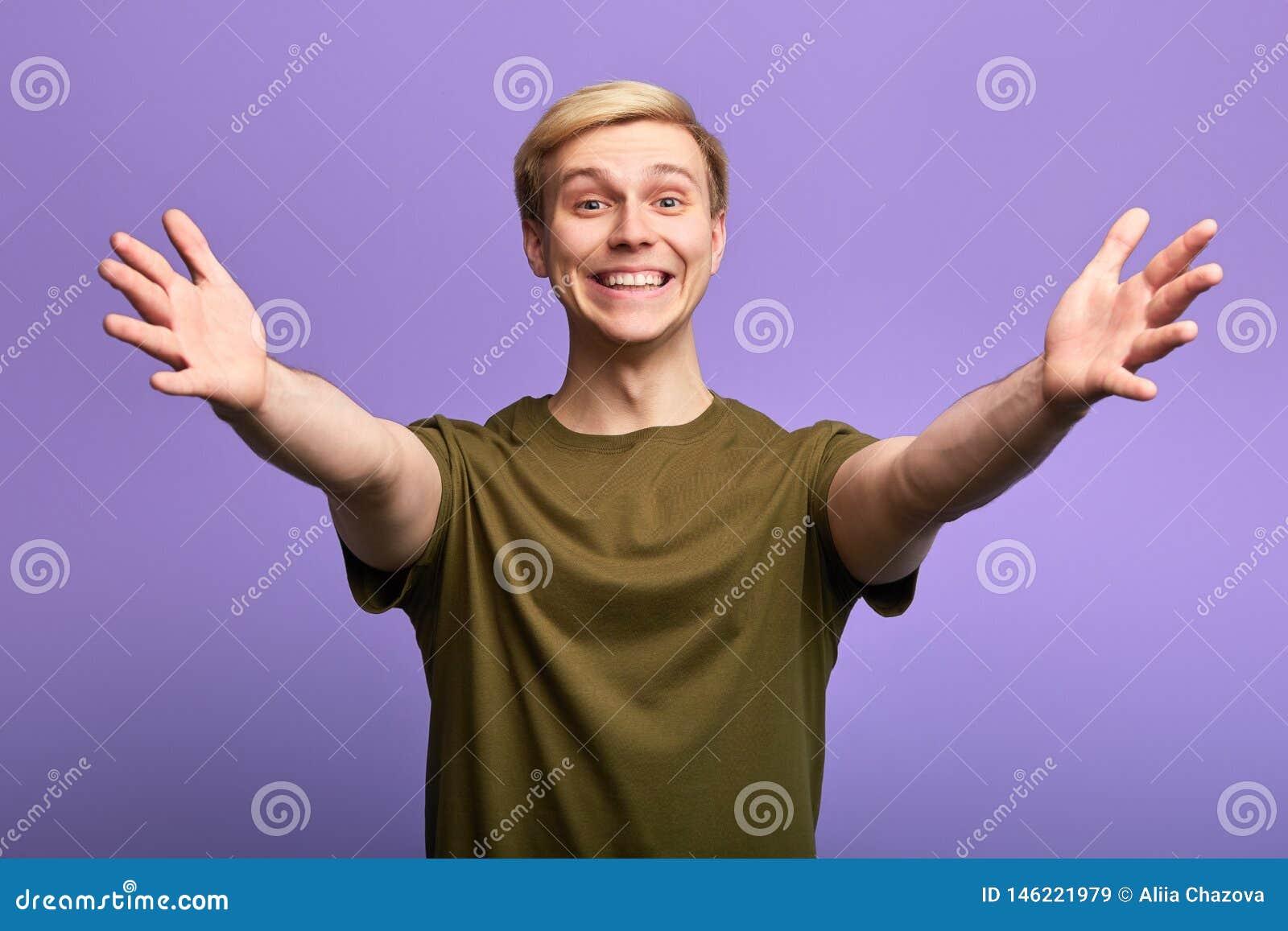 L homme bel heureux positif souhaitant la bienvenue à des personnes avec ses bras s est ouvert