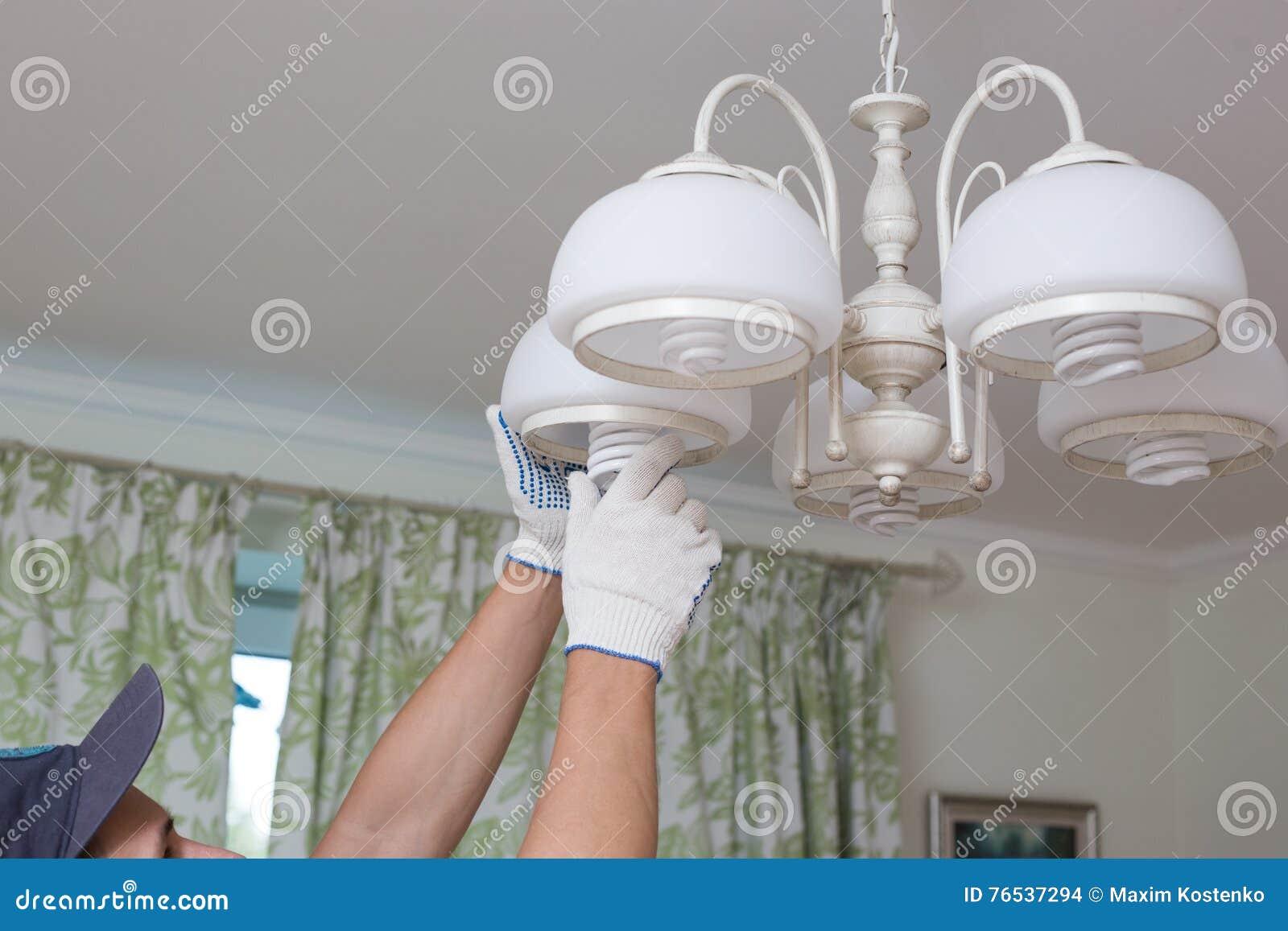 L homme change une ampoule électrique, rendement énergétique