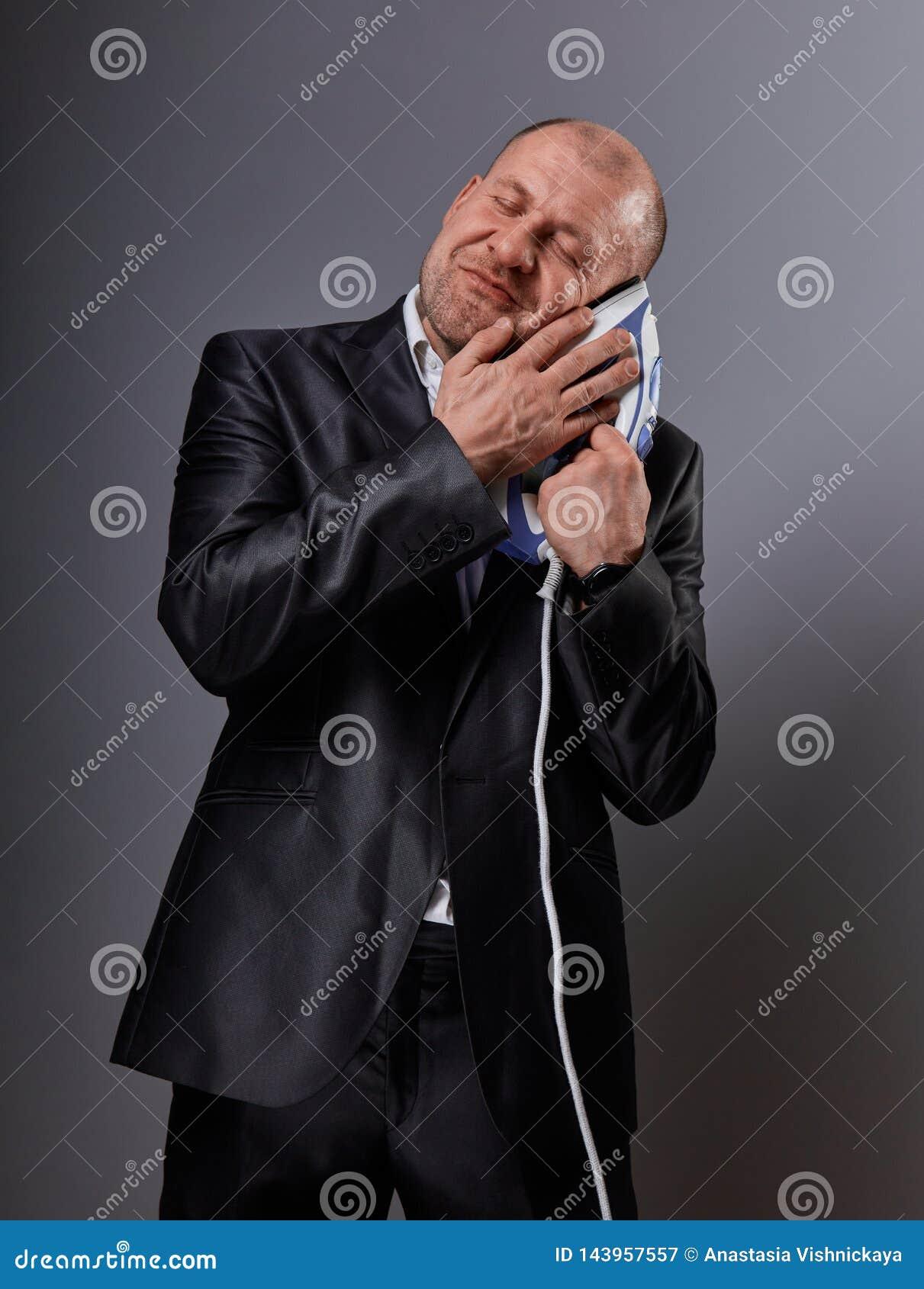 L homme comique heureux chauve d affaires tenant le fer à la maison de confort et le caressant avec amour et a clôturé apprécier