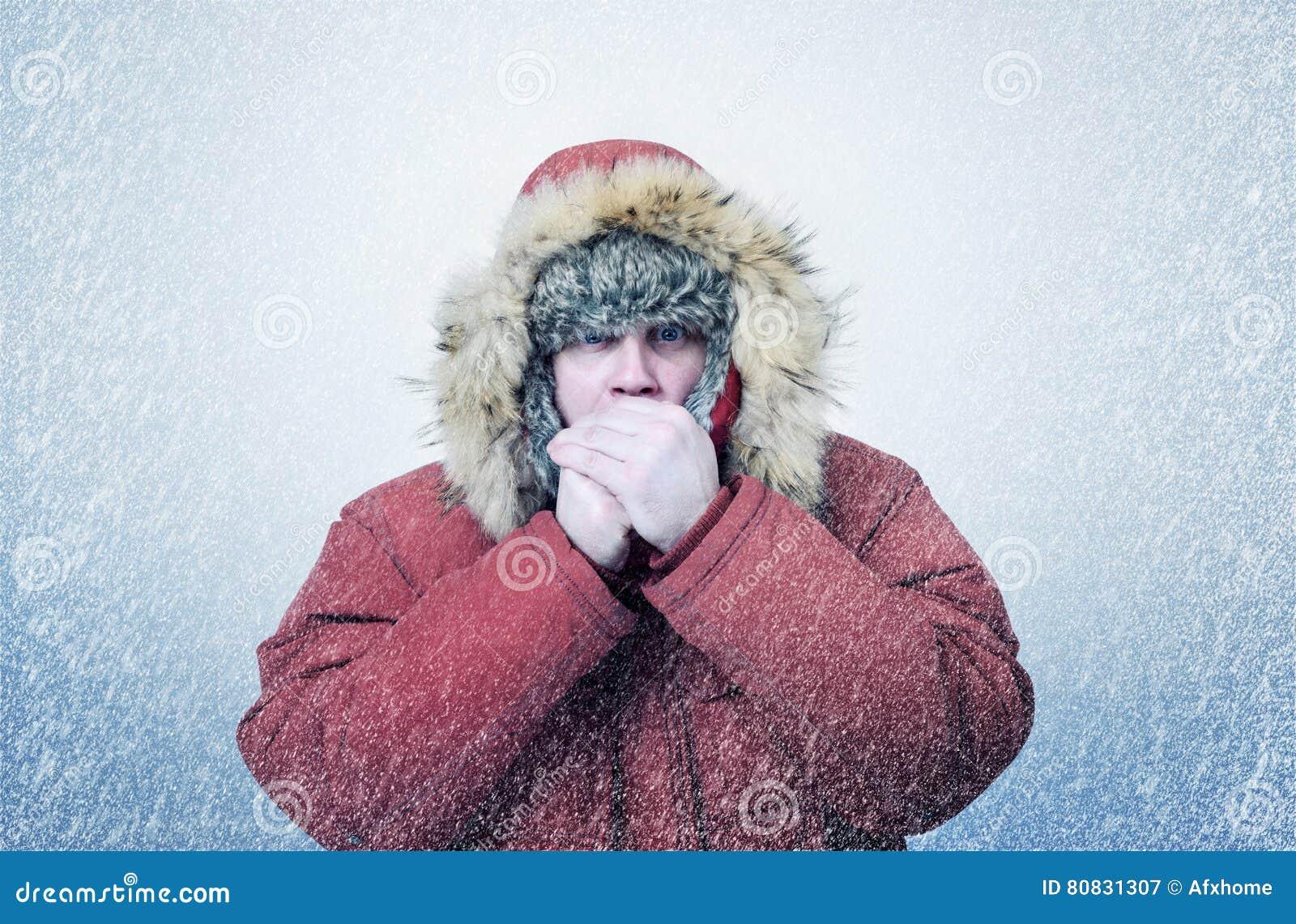 L homme congelé en hiver vêtx les mains de chauffage, froid, neige, tempête de neige