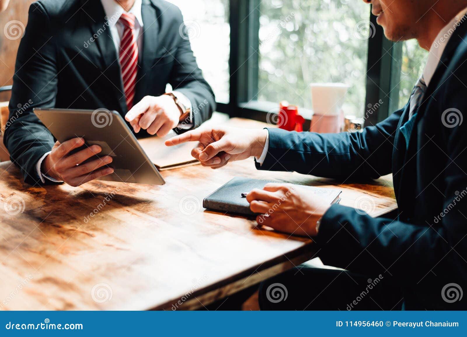 L homme d affaires deux reposant et regardant le comprimé, ils se réunissent au sujet du plan d action, du marketing et de financ